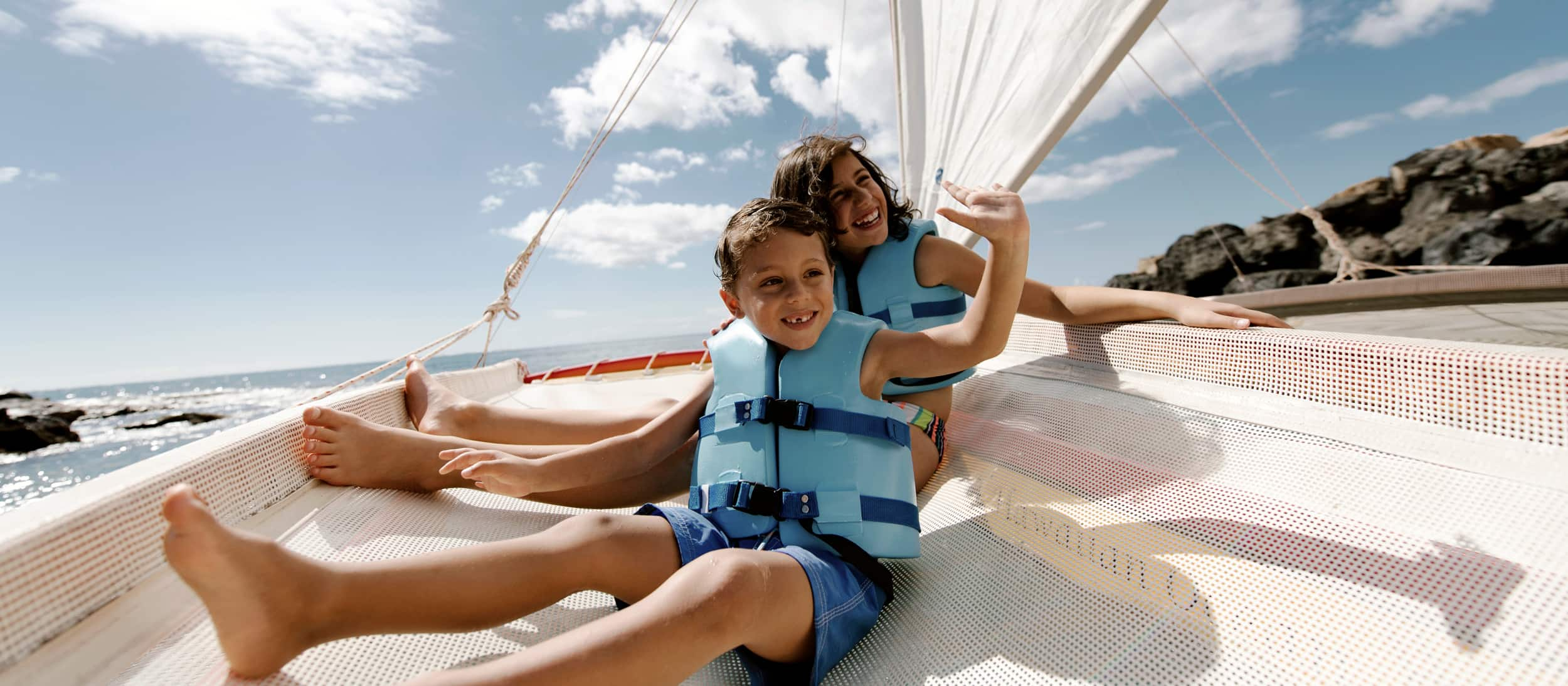A brother and sister, wearing matching life jackets, smile while riding on a catamaran