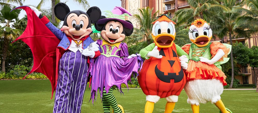 Mickey Mouse and Minnie, dressed in purple Halloween costumes, stand next to Donald Duck and Daisy, in pumpkin costumes