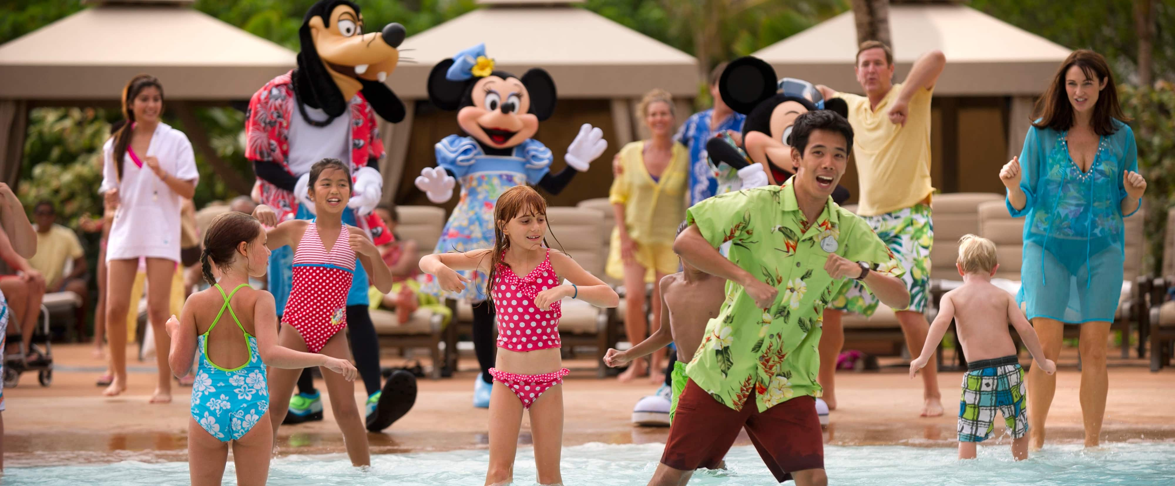 Kids, parents, Goofy, Minnie and Mickey do the chicken dance at a pool, led by a Cast Member