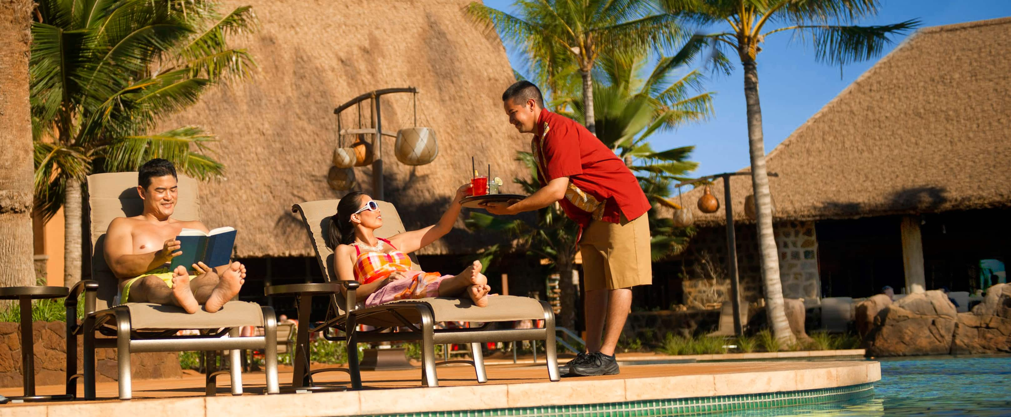 A server brings drinks to a woman on a poolside lounge chair while her husband reads a book