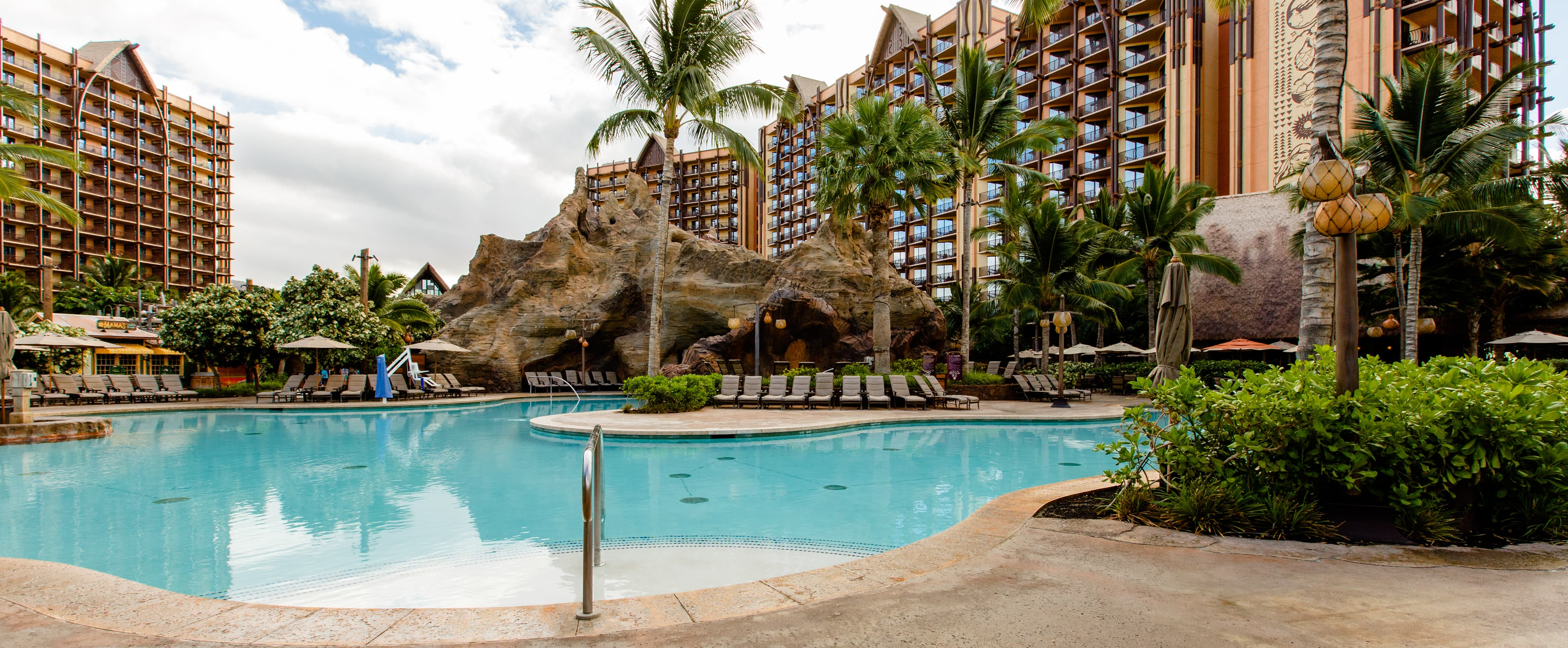 A section of Waikolohe Pool with rock caves, sunbathing areas and palm trees