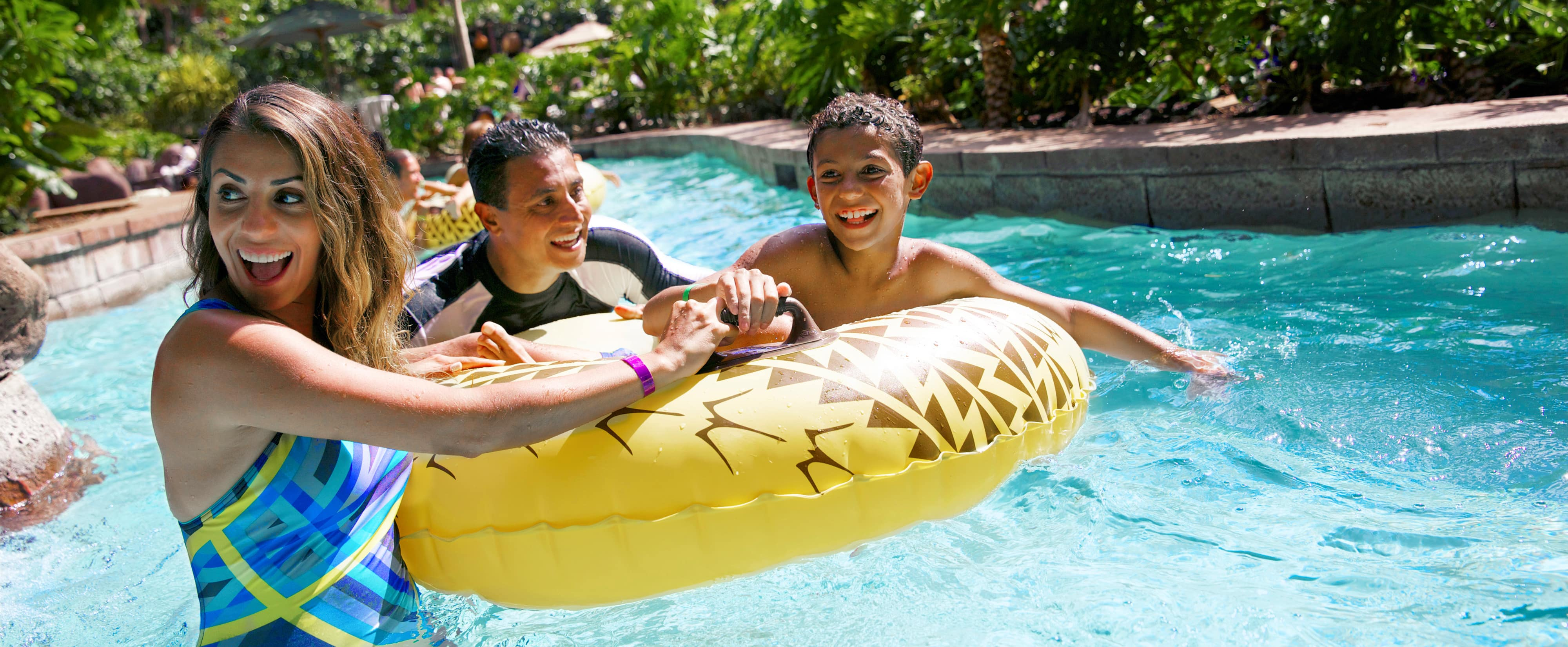 A smiling mother, father and son hold on to an inner tube as they move down a lazy river
