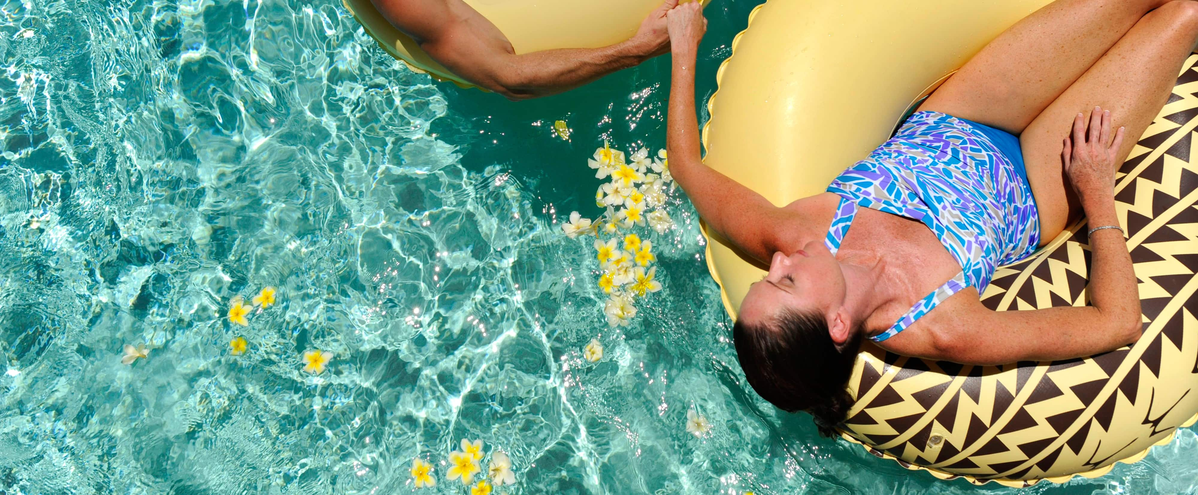 A woman in a swimsuit lying on an inner tube holds a man's hand in a pool with floating yellow flowers