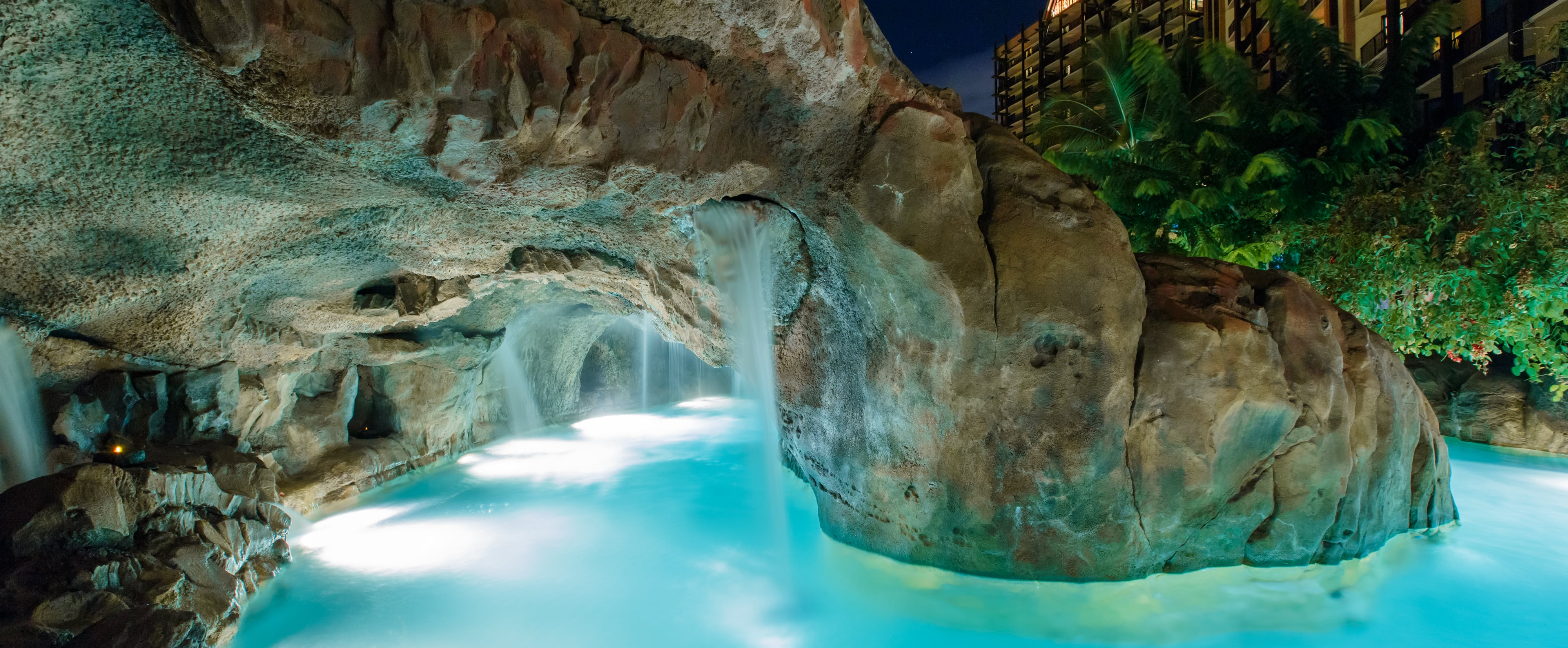 A lazy river winds through a dimly lit grotto with cascading water features and tropical landscaping