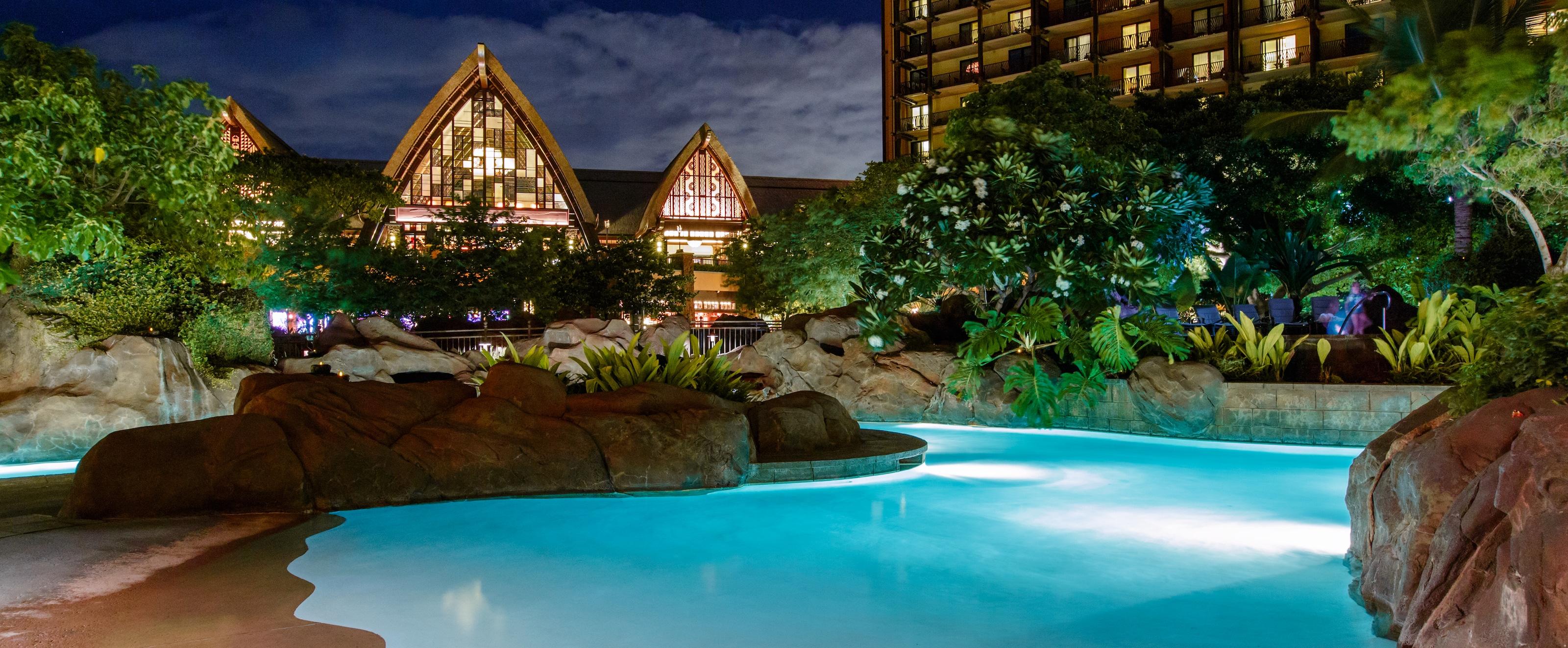 夜間にライトアップされた流れるプールと、その向こうに見えるリゾートのメイン・ビルディングの尖った屋根