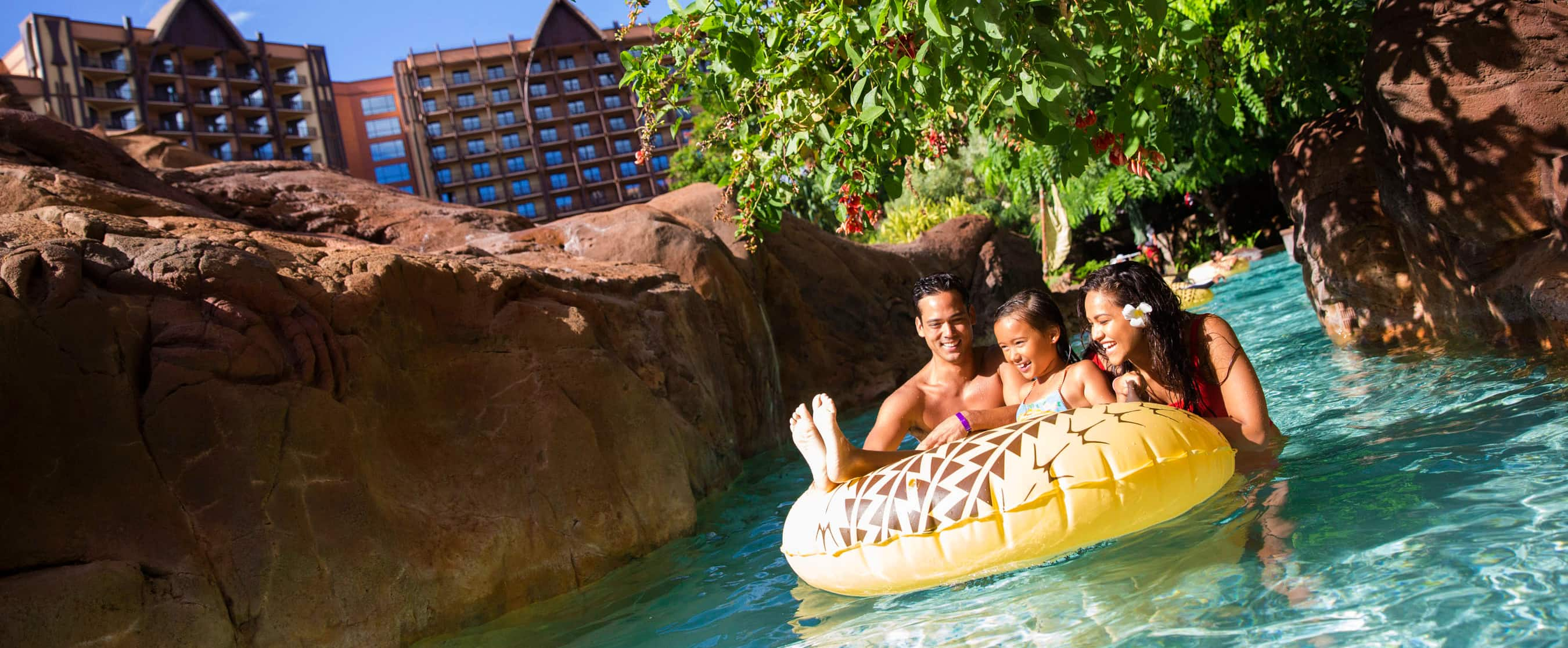 A girl on an inner tube in a lazy river with her father and mother, with rocky banks and a tree overhead