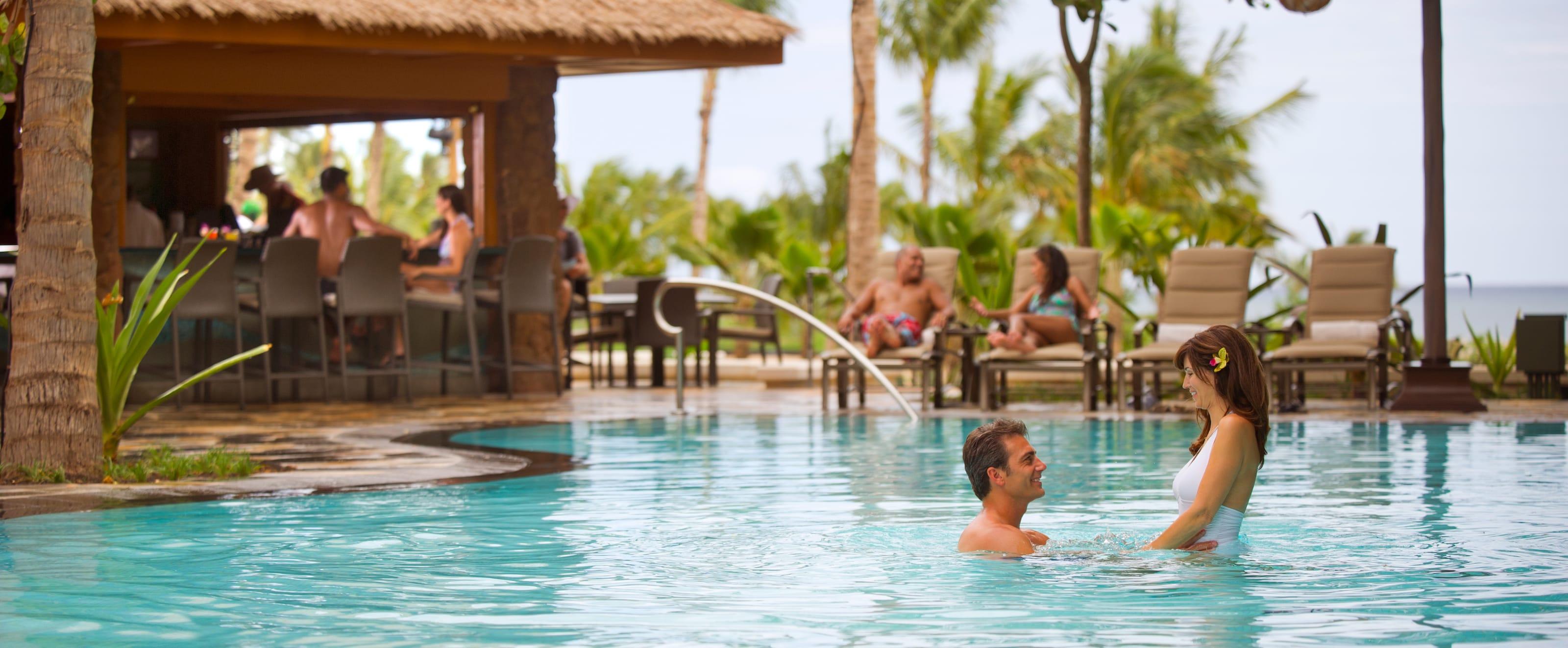 テンション・エッジ・プールで女性を抱え上げる男性と、デッキチェアでくつろぎ、バーでドリンクを楽しむカップル達