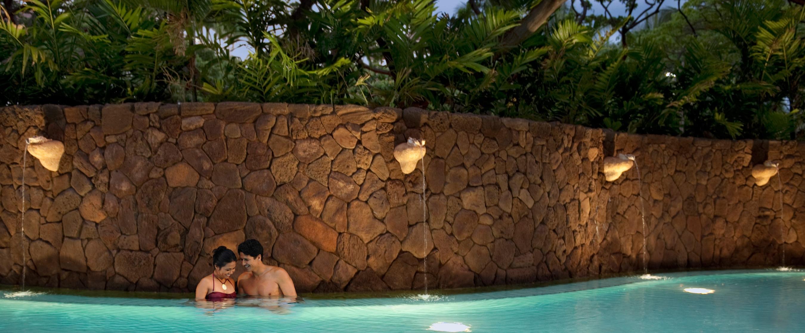 貝殻のような噴水をアクセントに、カーブした高い岩壁を配したプールで夕暮れを楽しむ男女