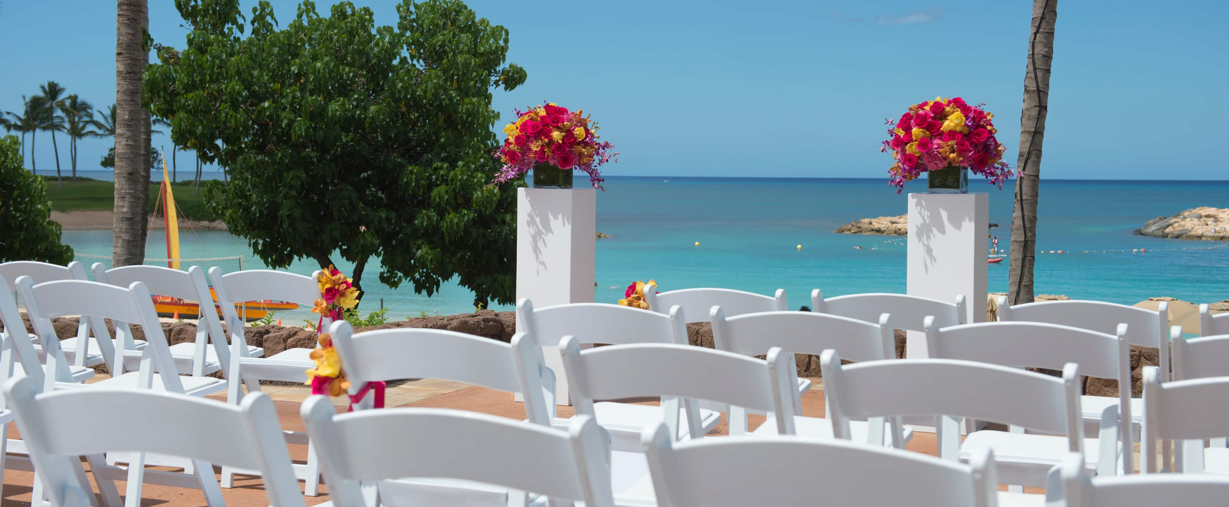 Rows of white chairs and 2 pillars with brightly colored floral arrangements overlook an azure ocean