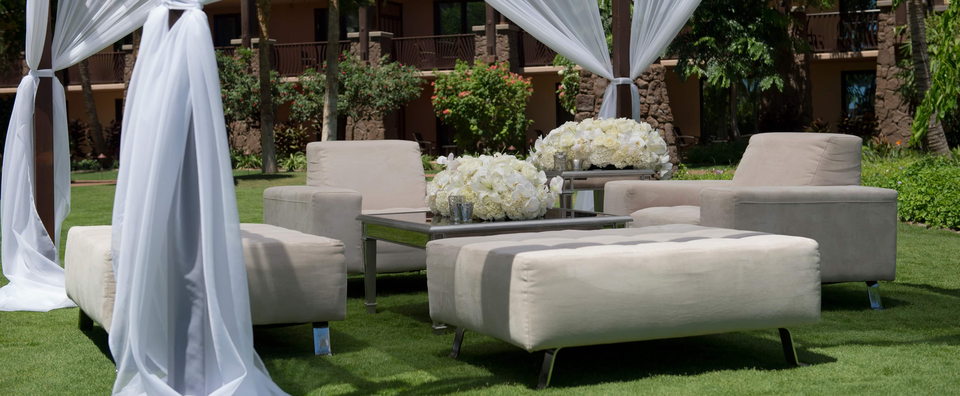 Gray armchairs and ottomans around 2 white floral centerpieces under a white-draped canopy on a lawn
