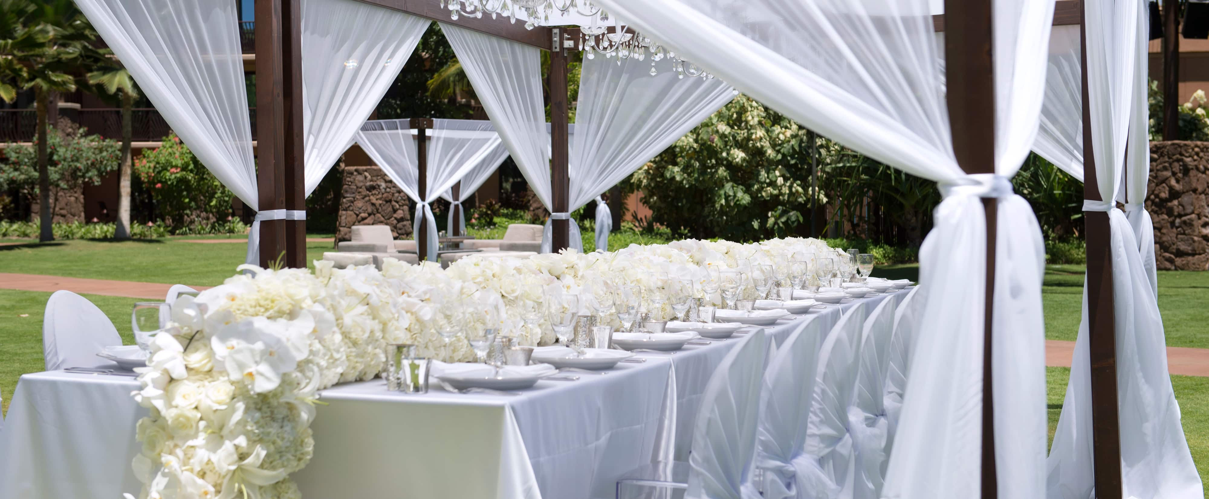 A wedding party banquet table decorated with a garland of white roses and orchids under a canopy on a lawn