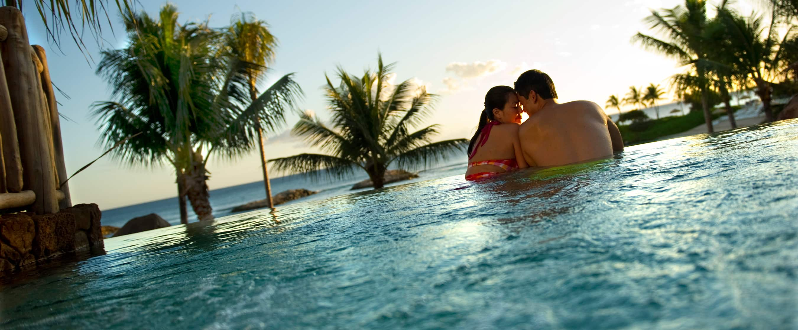 A young couple embraces while unwinding in a whirlpool spa as the sun sets along the oceanic horizon