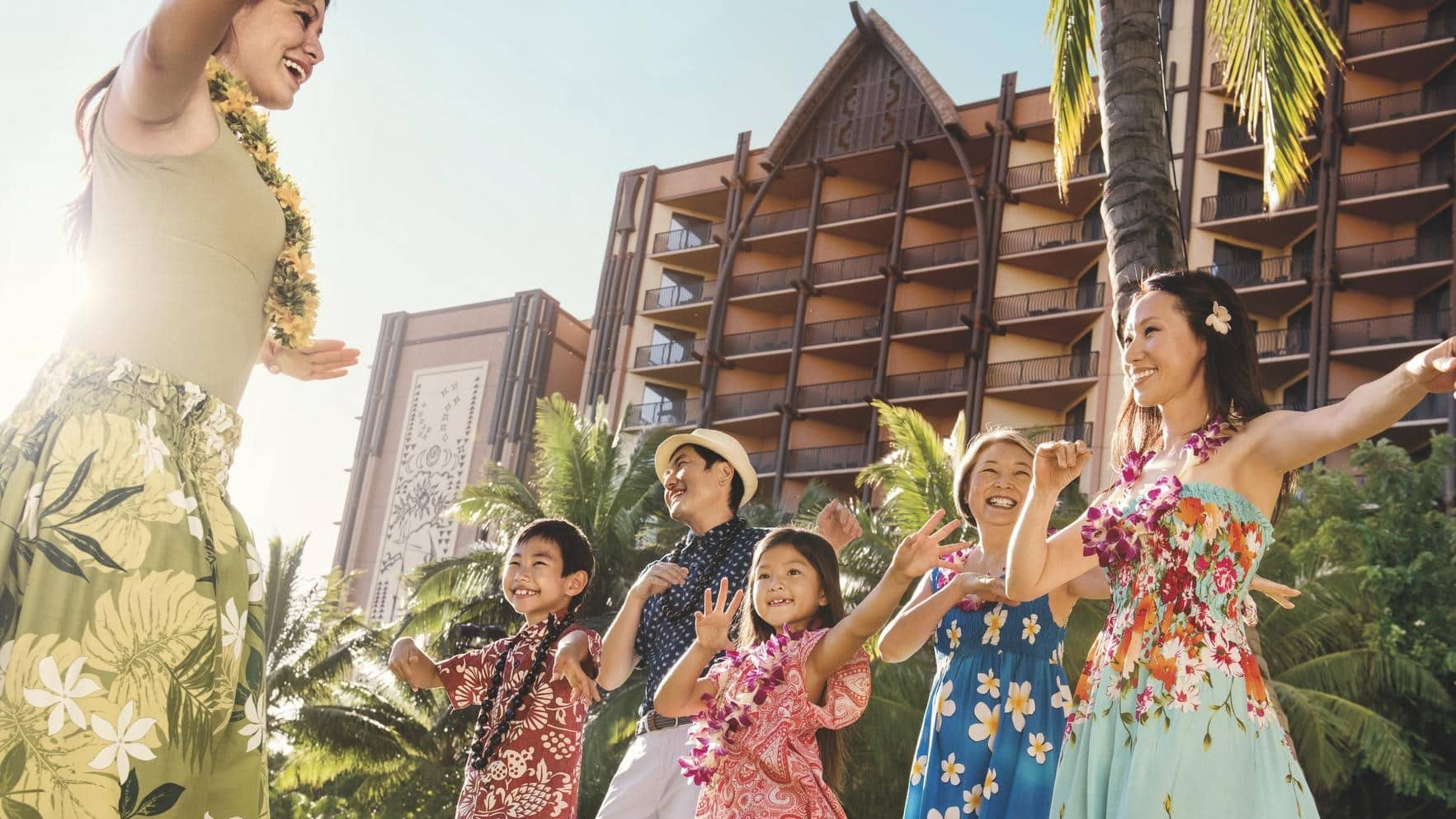 A cast member and a family dancing with the towers of Aulani resort in the background