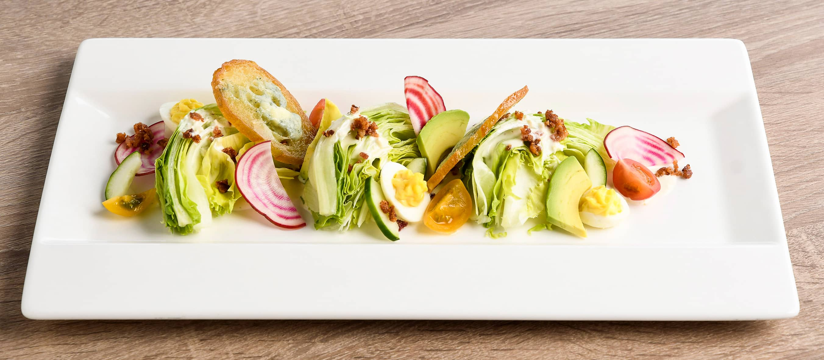 A rectangular plate containing a wedge salad with tomatoes, radish, eggs, avocado, bacon and bread crisps