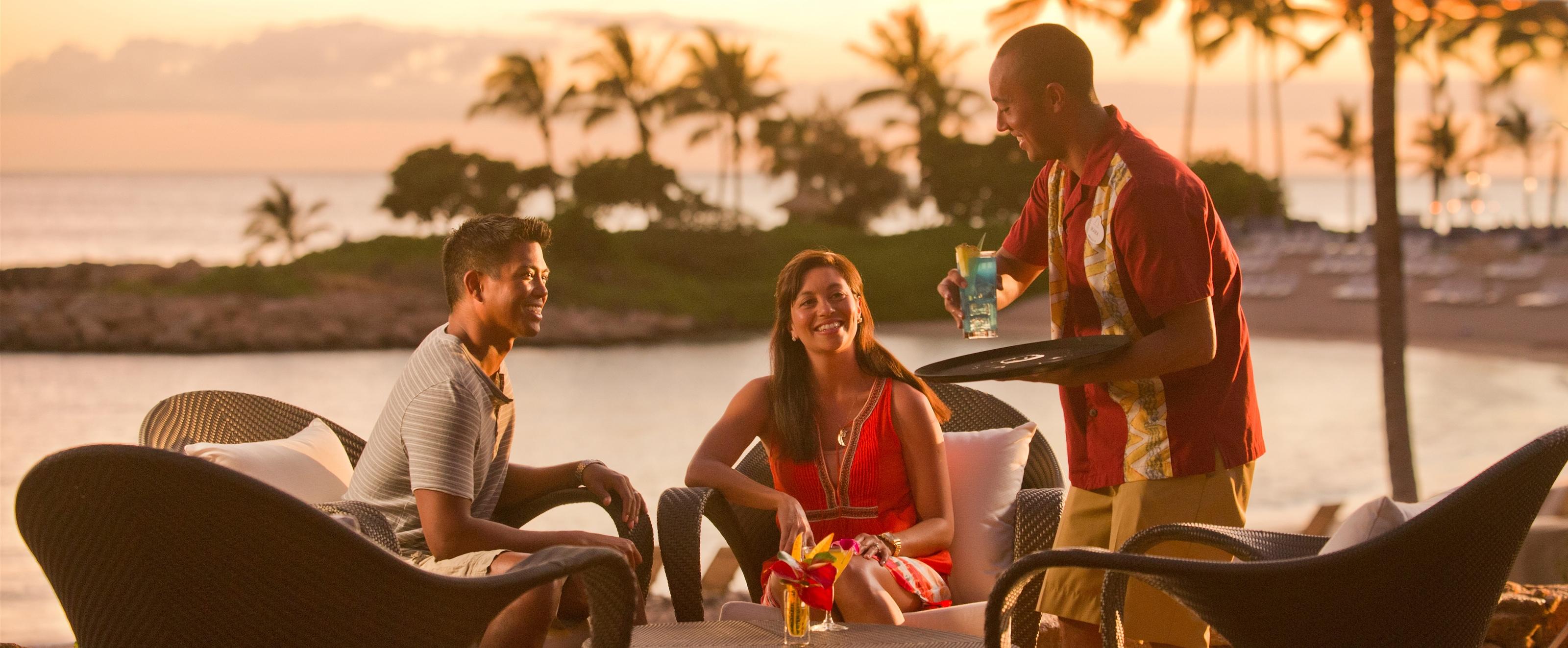 オーシャン・ビューの屋外テーブルでくつろぐカップルに、トロピカルカクテルをサービスする笑顔のウェイター