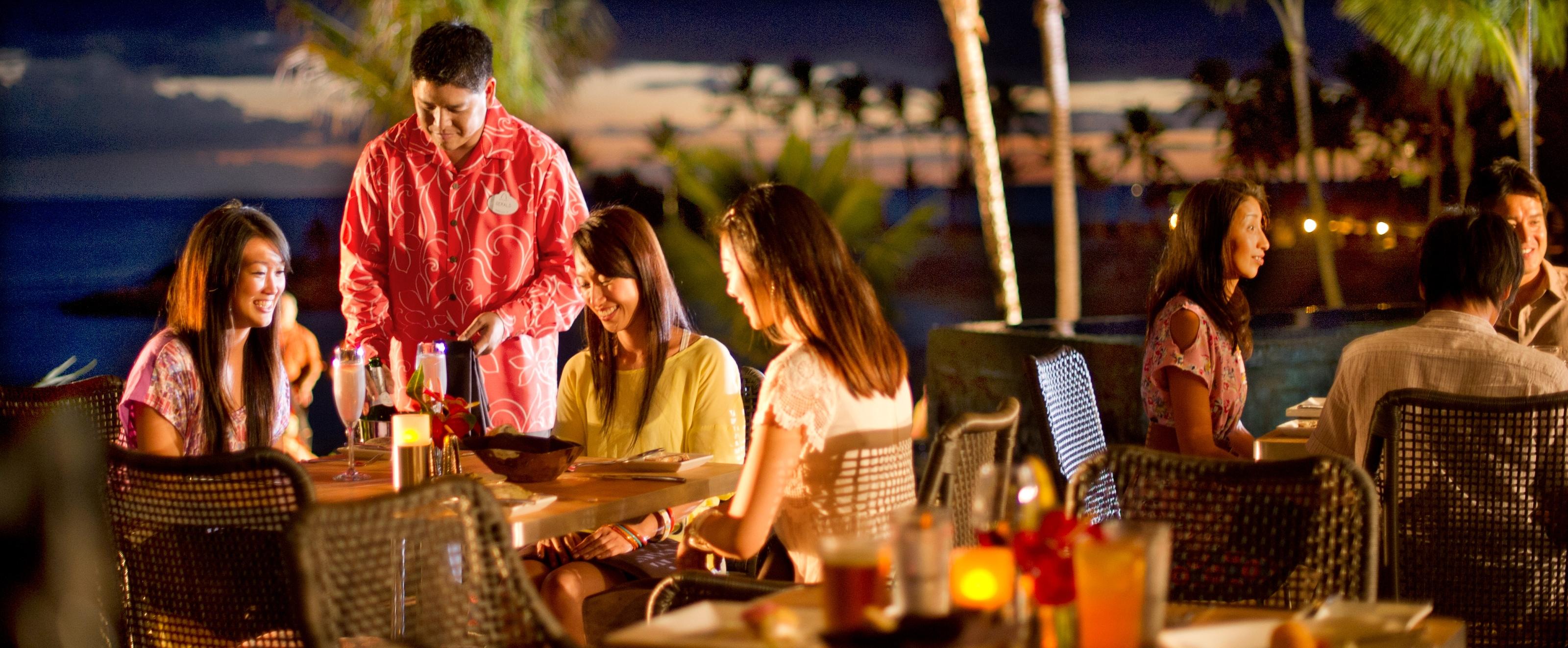 屋外でテーブルでのシャンパン・サービスとディナーを楽しむ 3 人の若い女性