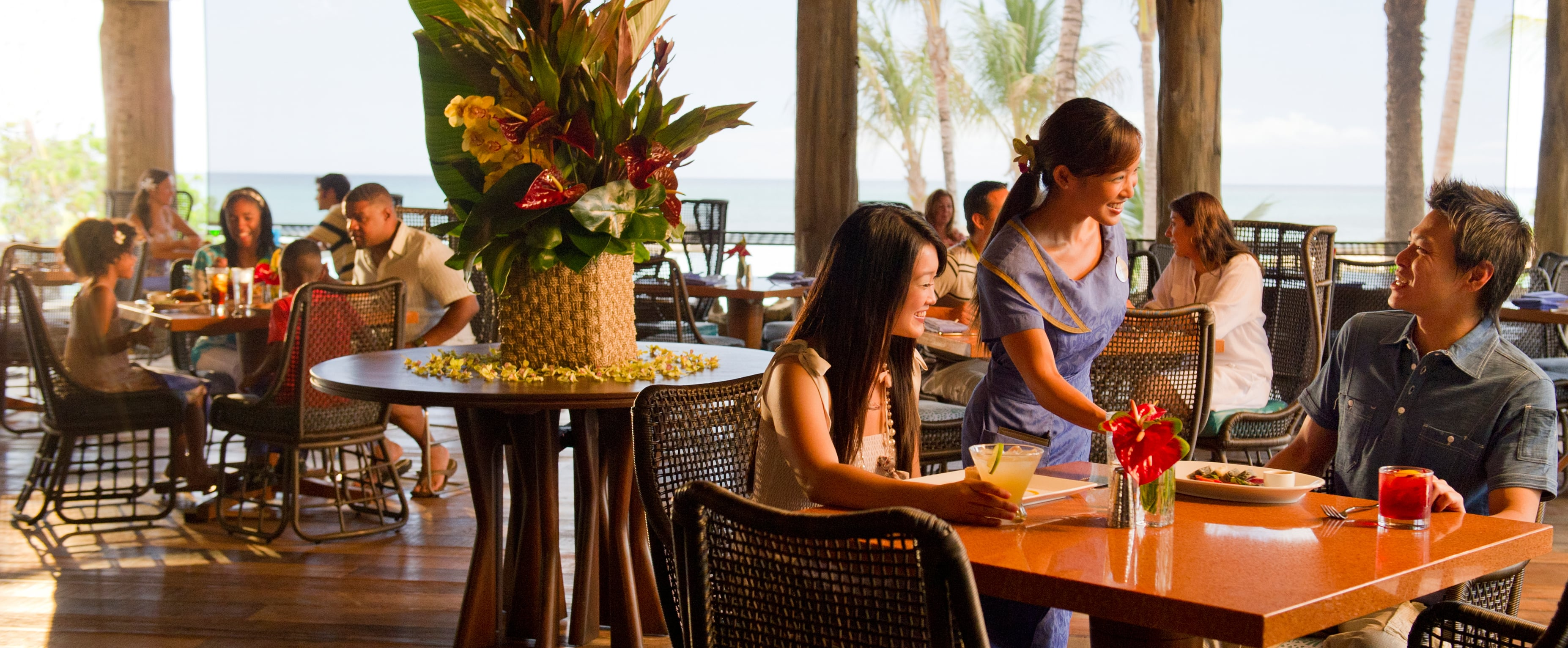 A friendly server interacts with a couple seated on a covered patio with a tropical floral arrangement