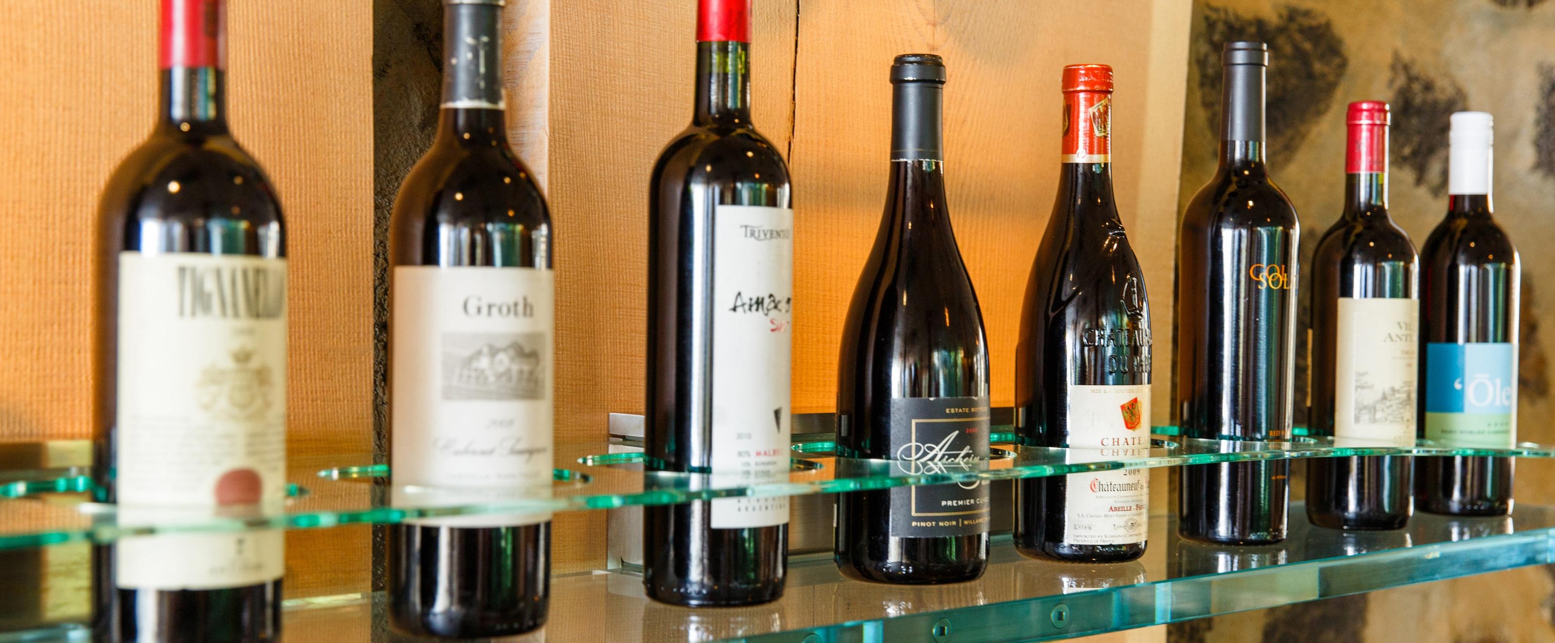 丸いスロットのガラス棚に置かれた 8 本の赤ワインのボトル