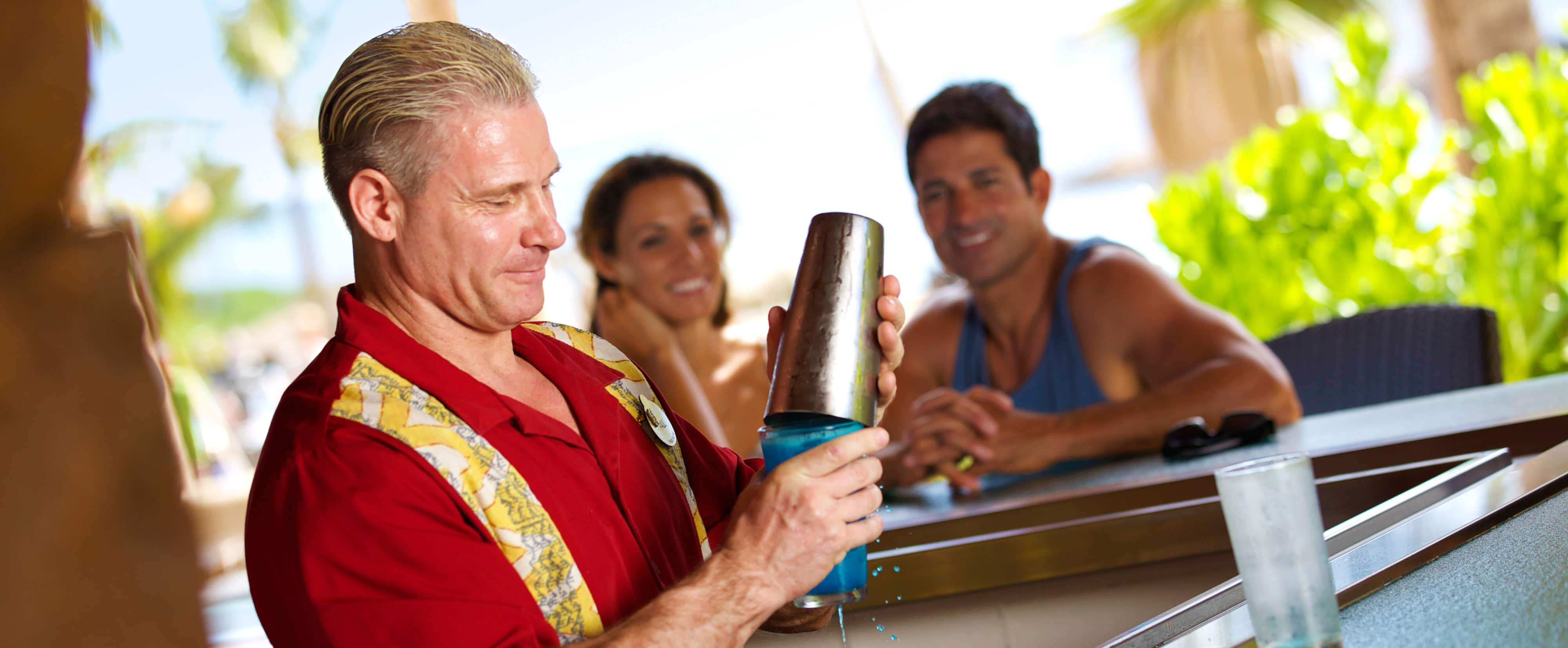 A bartender mixes a blue drink with a cocktail shaker while a smiling couple sitting at the bar watches