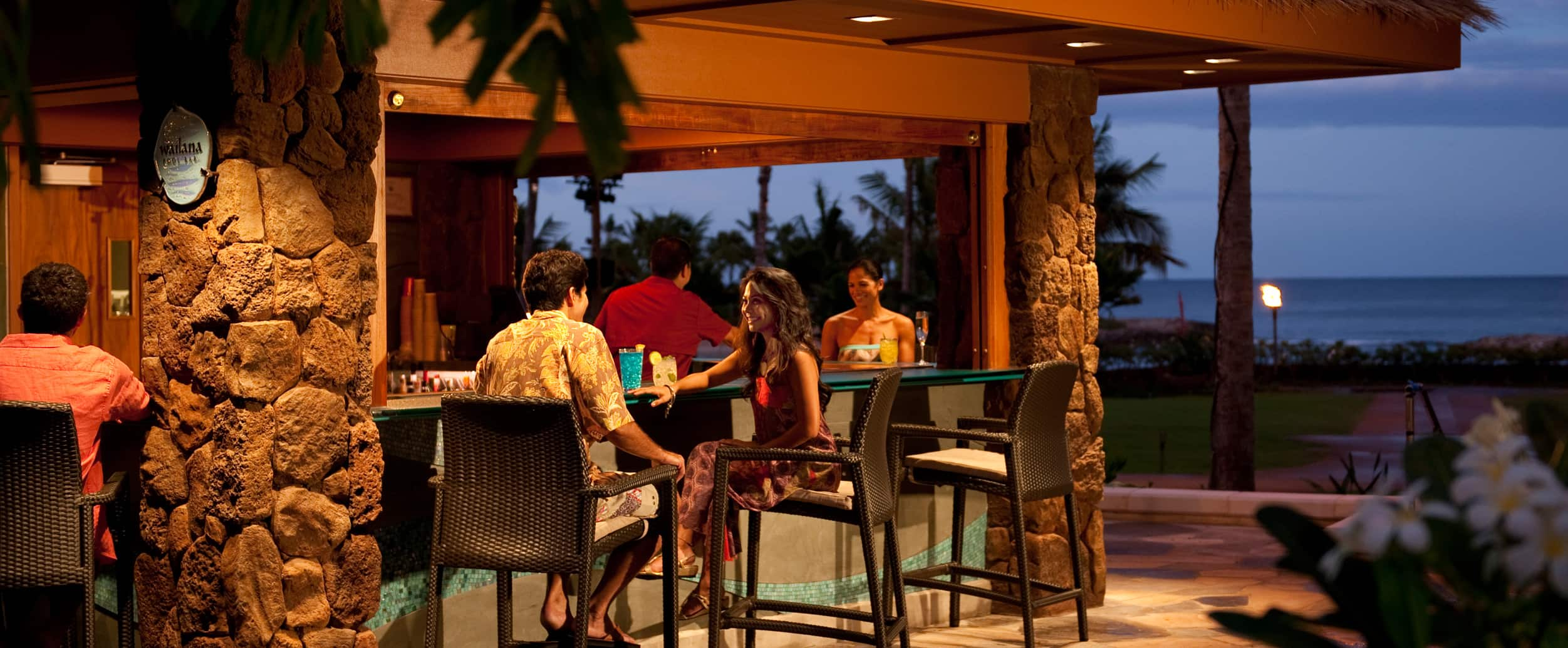 A man and a woman in resort wear enjoy evening cocktails at a thatched outdoor bar with an ocean view