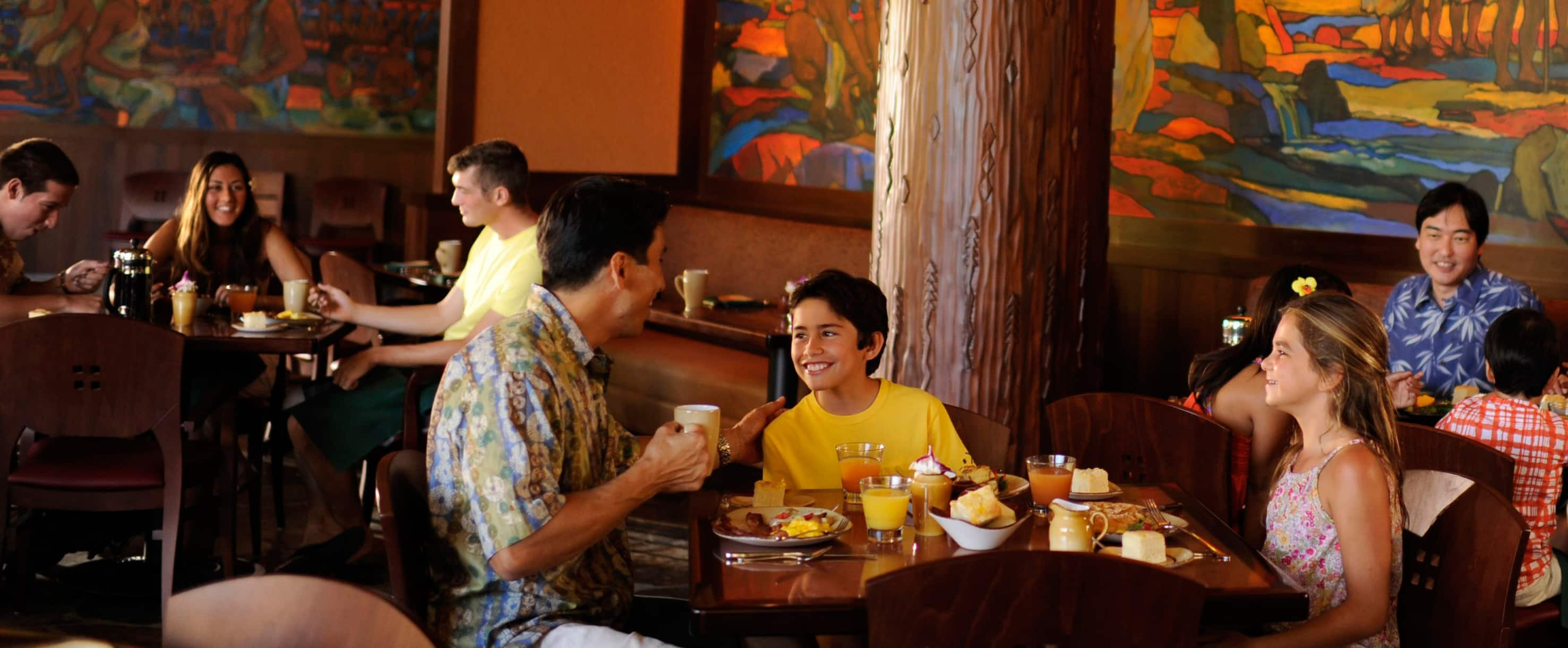 A Father And Son In An Animated Conversation At Breakfast While Young Daughter Looks On