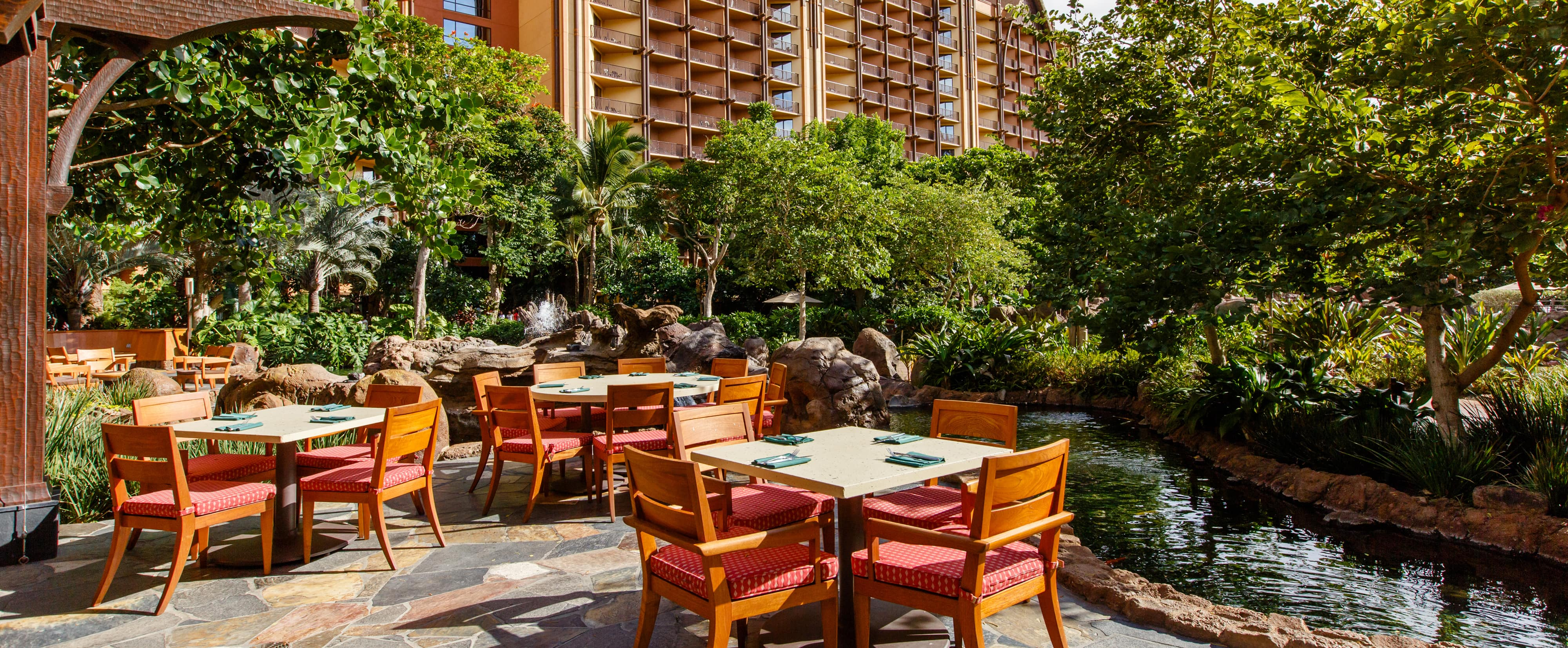 Three outdoor patio tables overlook a lushly landscaped man-made stream with rock features