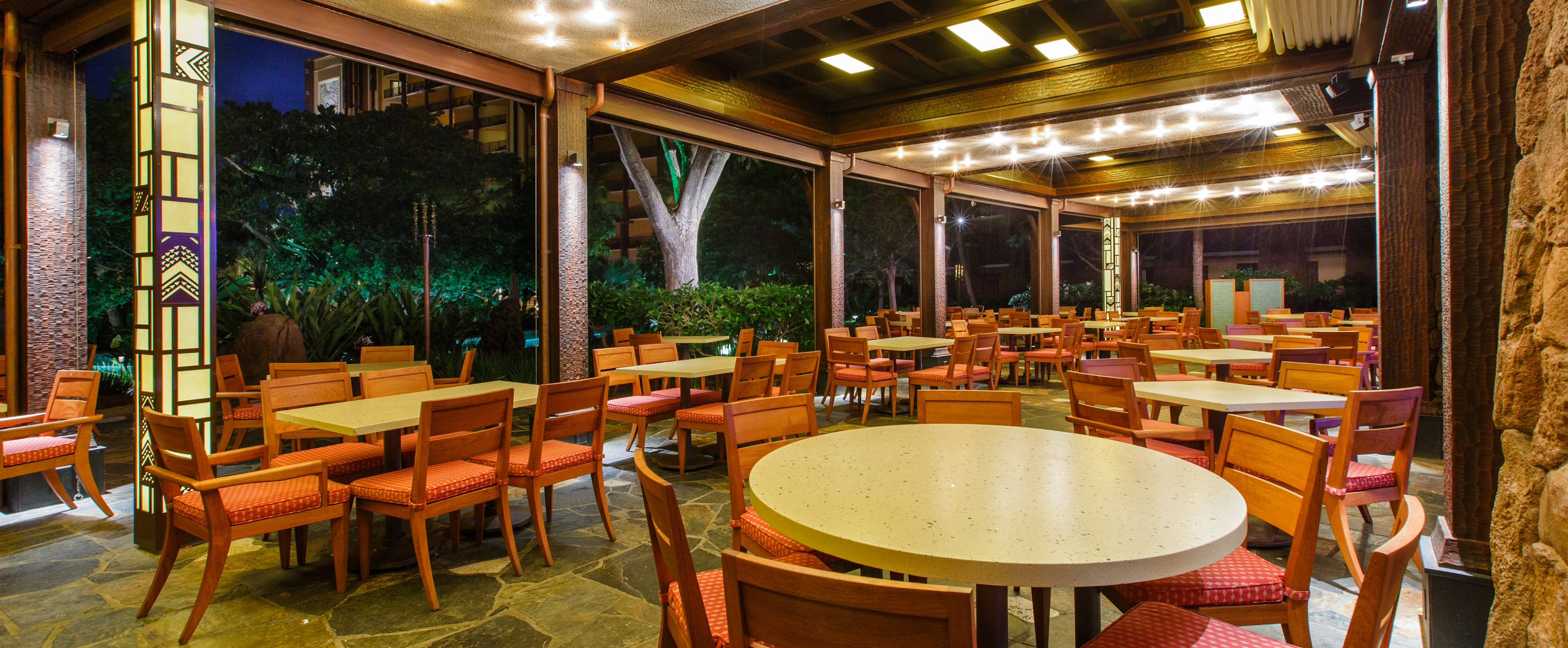 Tables on a large covered patio, lit up at night