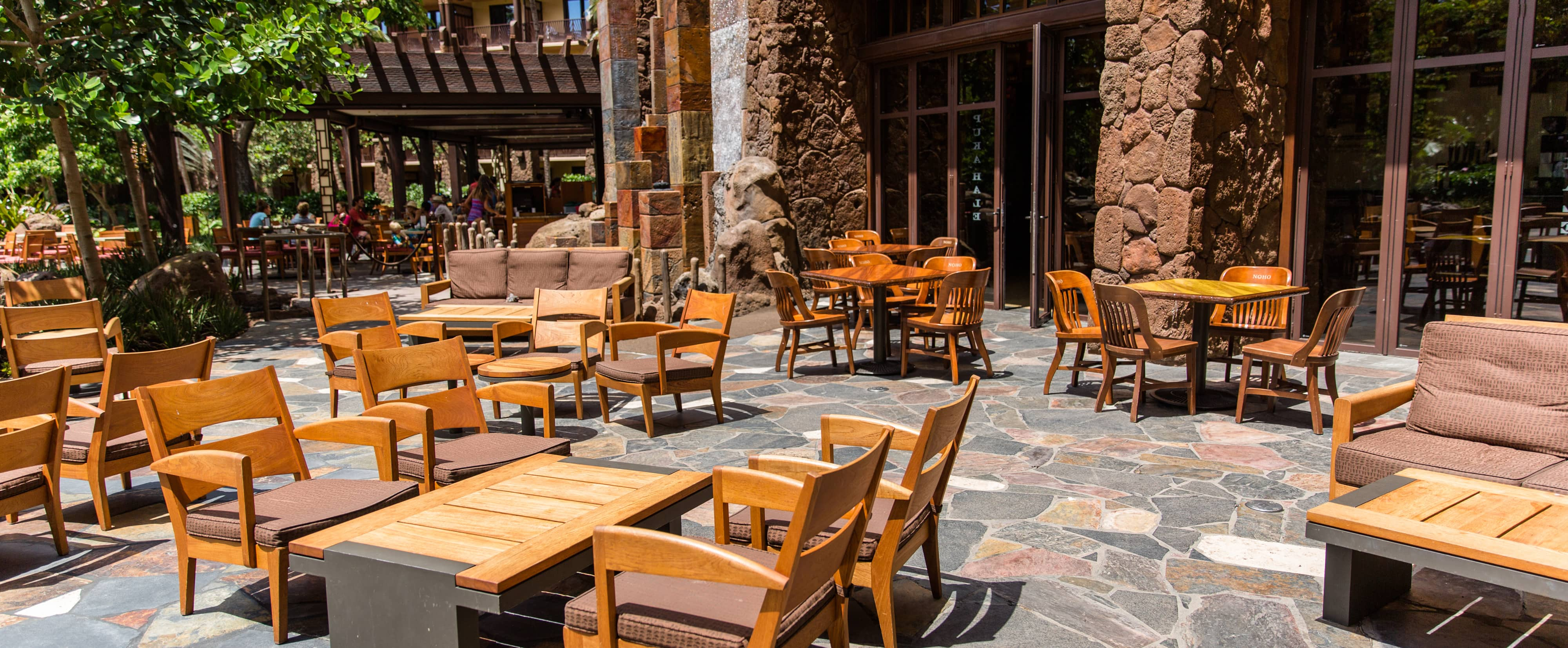 Outdoor tables and 2 couches on a flagstone paved patio