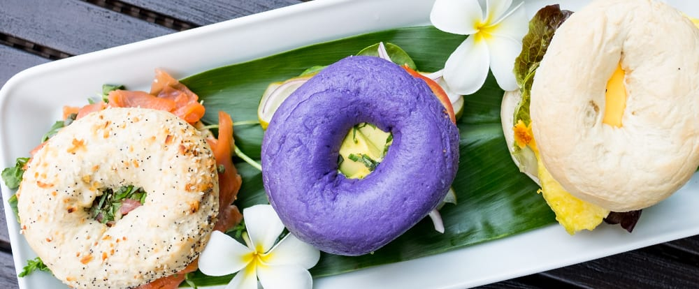 Two plumeria blossoms on a plate next to 3 mini bagel sandwiches