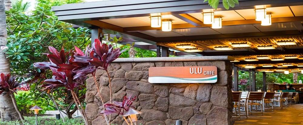 A sign reads Ulu Cafe, with tables on a covered patio looking out on a garden of tropical plants