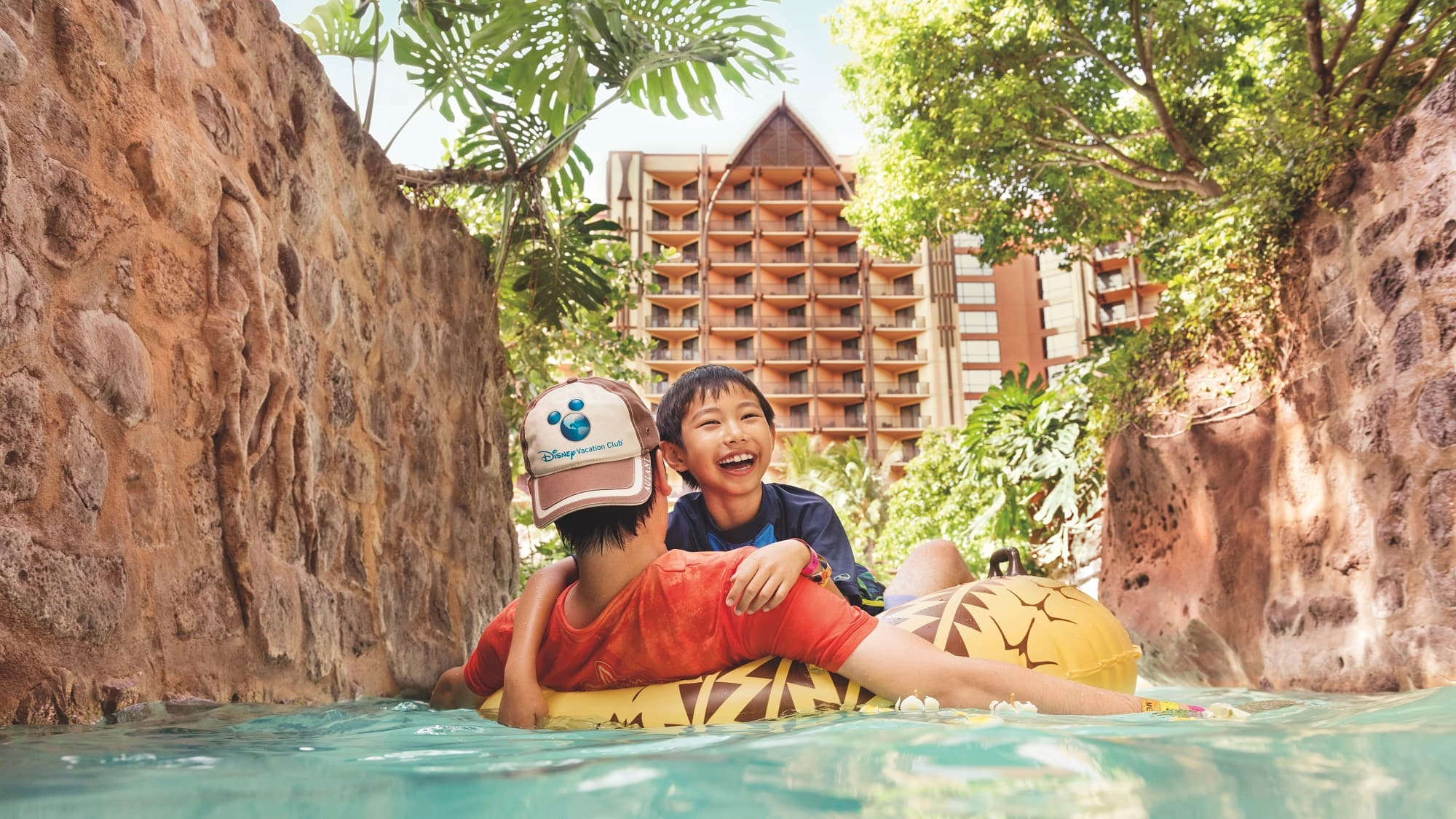 A father and son floating on a raft along the lazy river at Aulani Resort