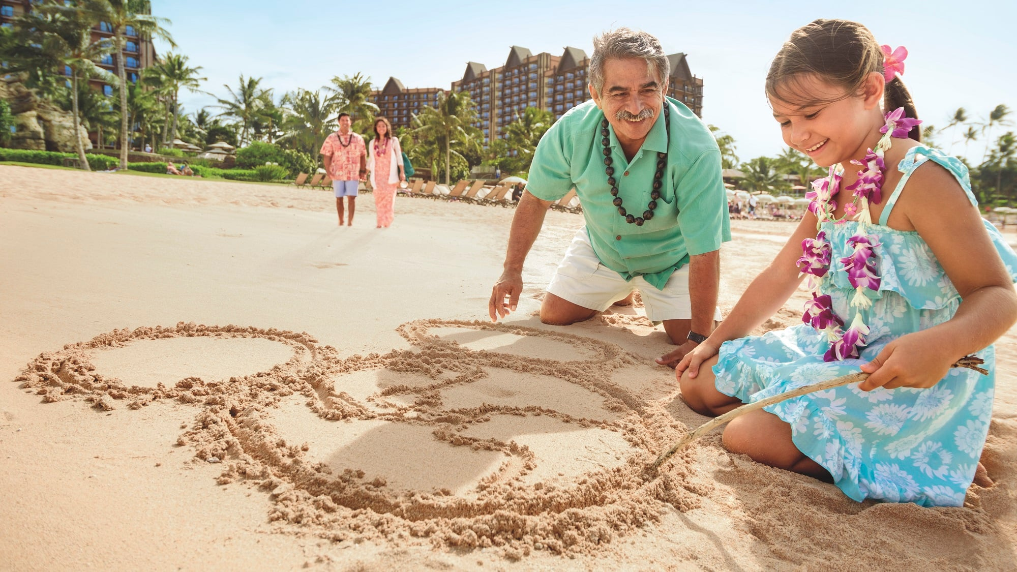 A girl and her grandfather drawing in the sand on the beach at Aulani Resort