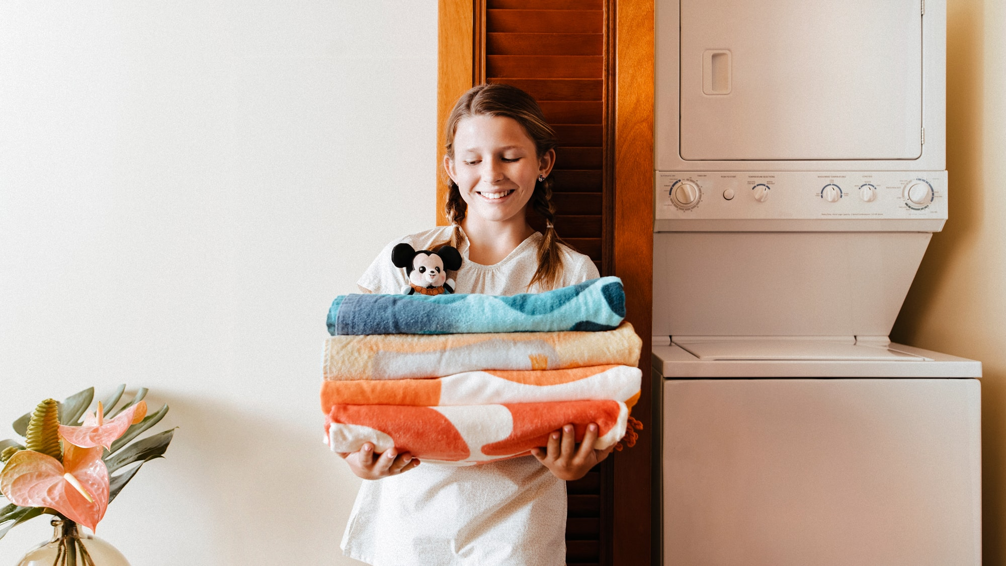 A young girl holding a stack of towels in the laundry area of a Villa