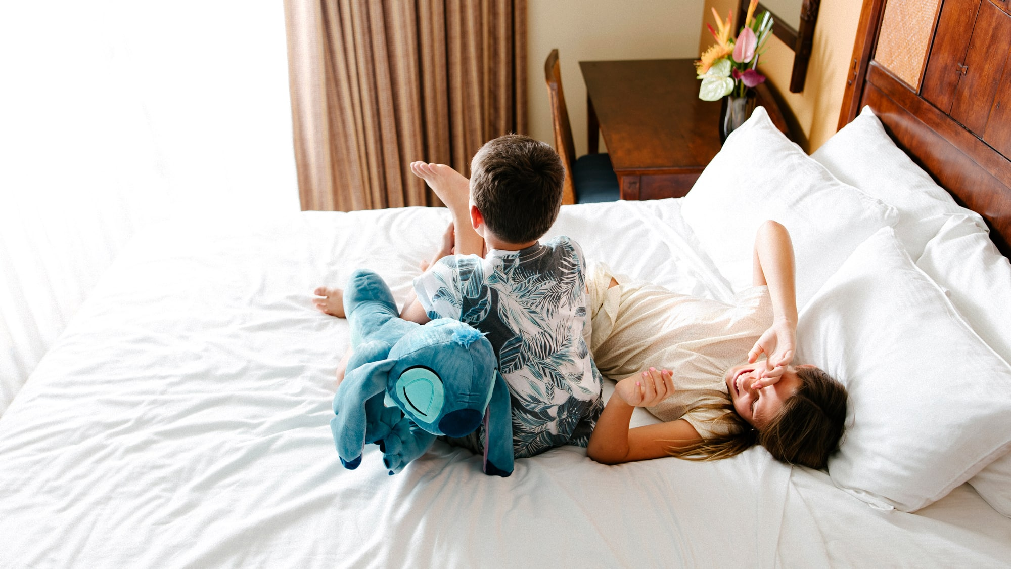 Two children lounging on a hotel bed