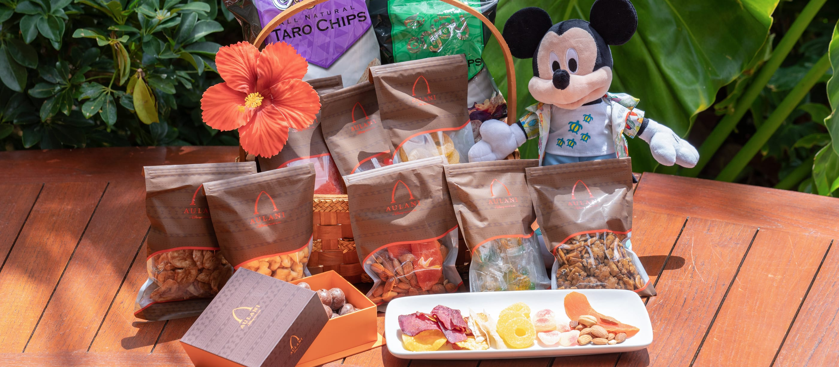 Aulani Friendship Basket gift basket including an array of individually packaged snacks and a plush Mickey Mouse