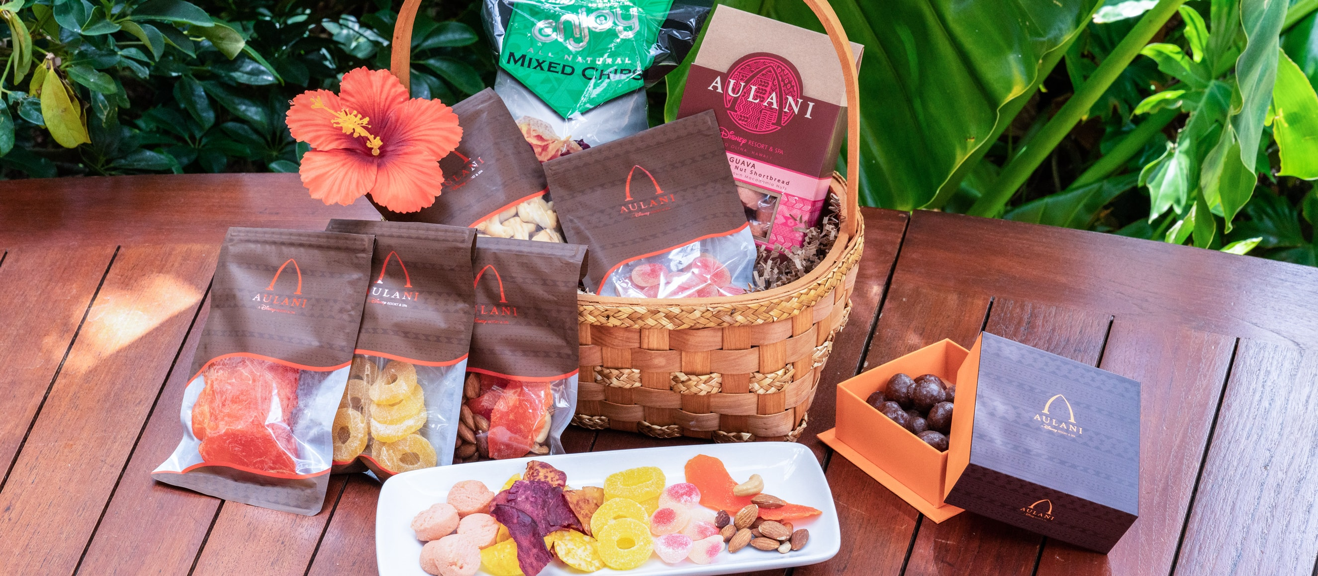 A gift basket of treats, including an Aulani cookie box, accompanied by snacks arrayed on a platter