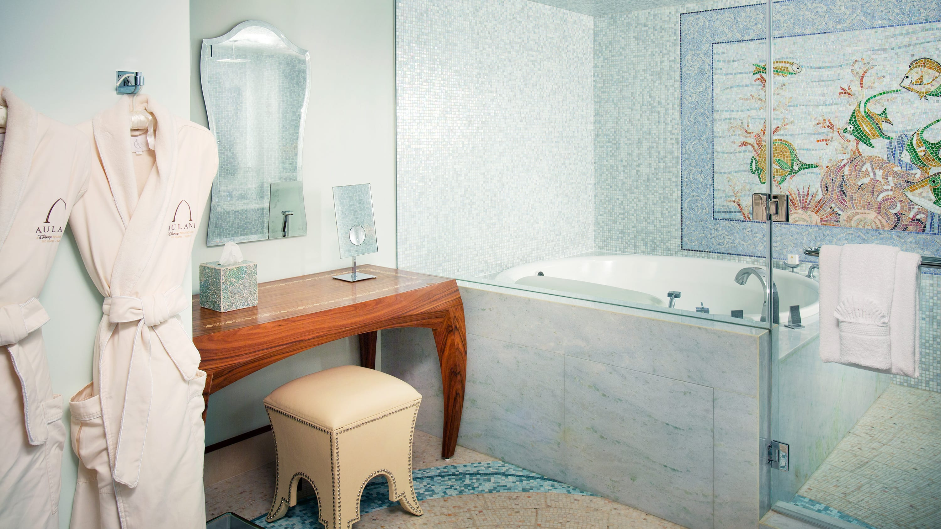 A bathtub, 2 robes, a stool, a vanity and towels