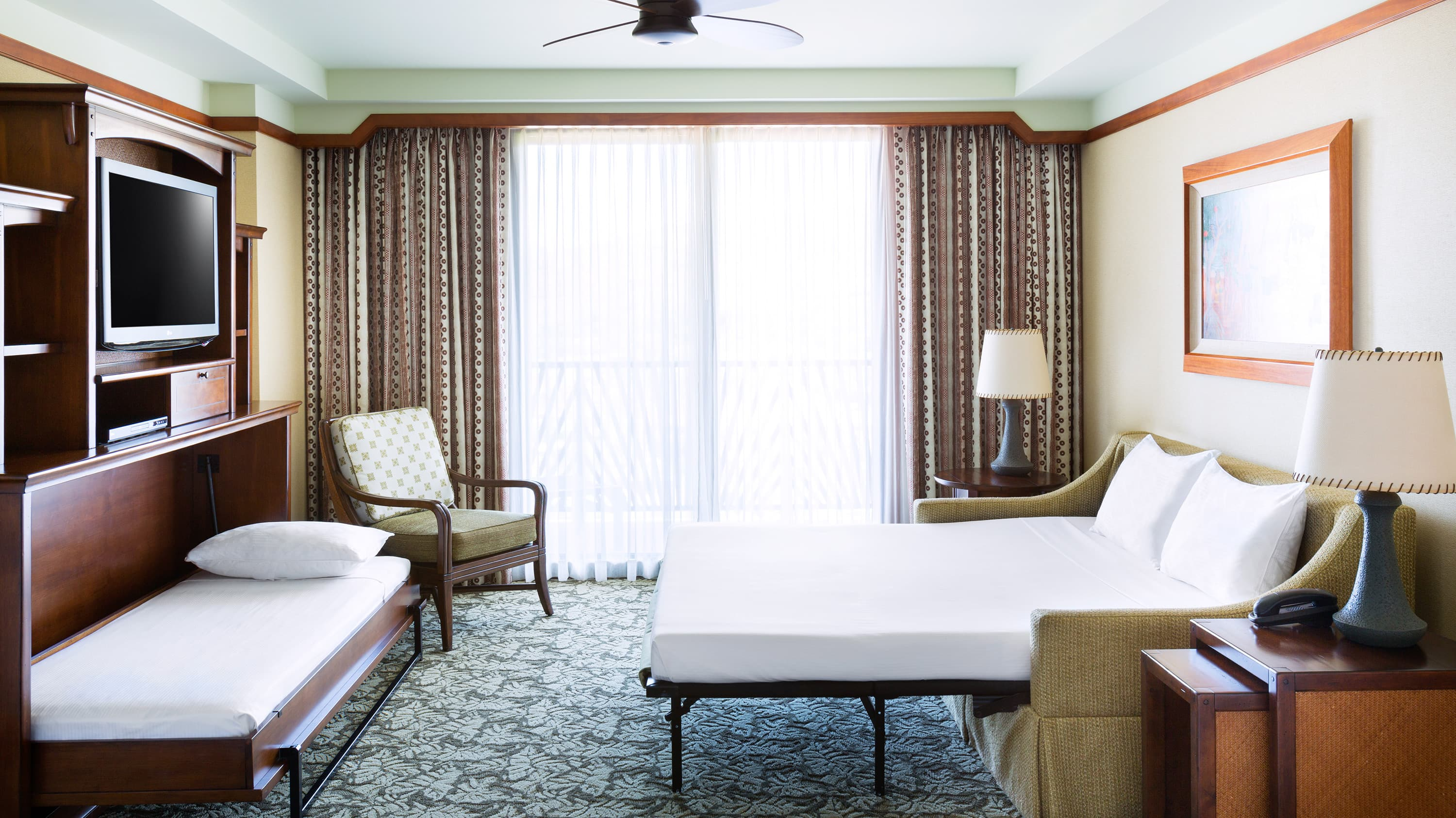 A room with 2 pull out beds, a TV, a chair, 2 lamps and curtains