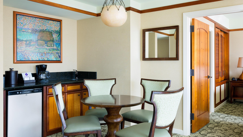 テーブル、椅子 4 脚、鏡、ミニ冷蔵庫、コーヒーメーカーが設置され、ドアの横にシンクがあるお部屋