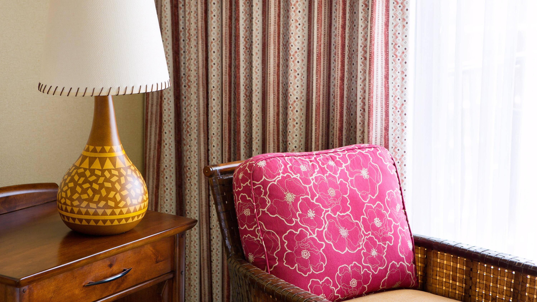 A chair near a lamp and curtains