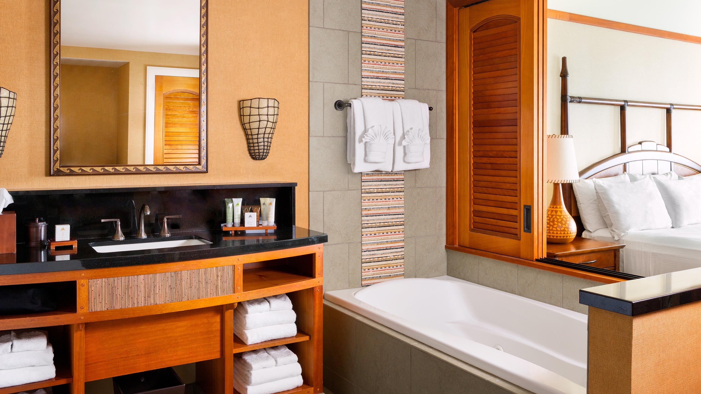洗面台、鏡、洗面用具、タオルが置かれ、仕切りの近くにバスタブのあるバスルーム