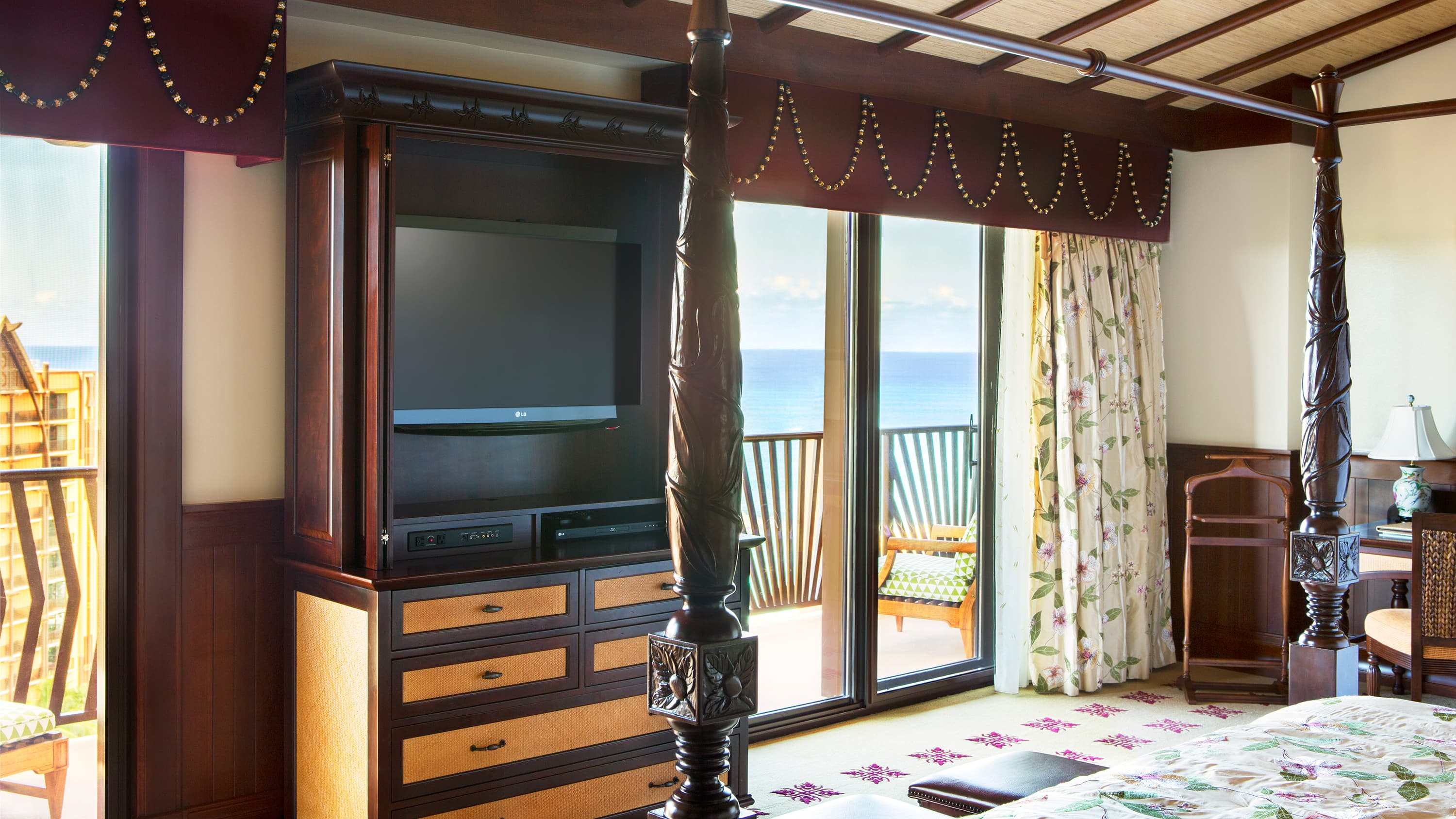 A room with a four poster bed, a TV, an armoire, a chair, a lamp and balcony access