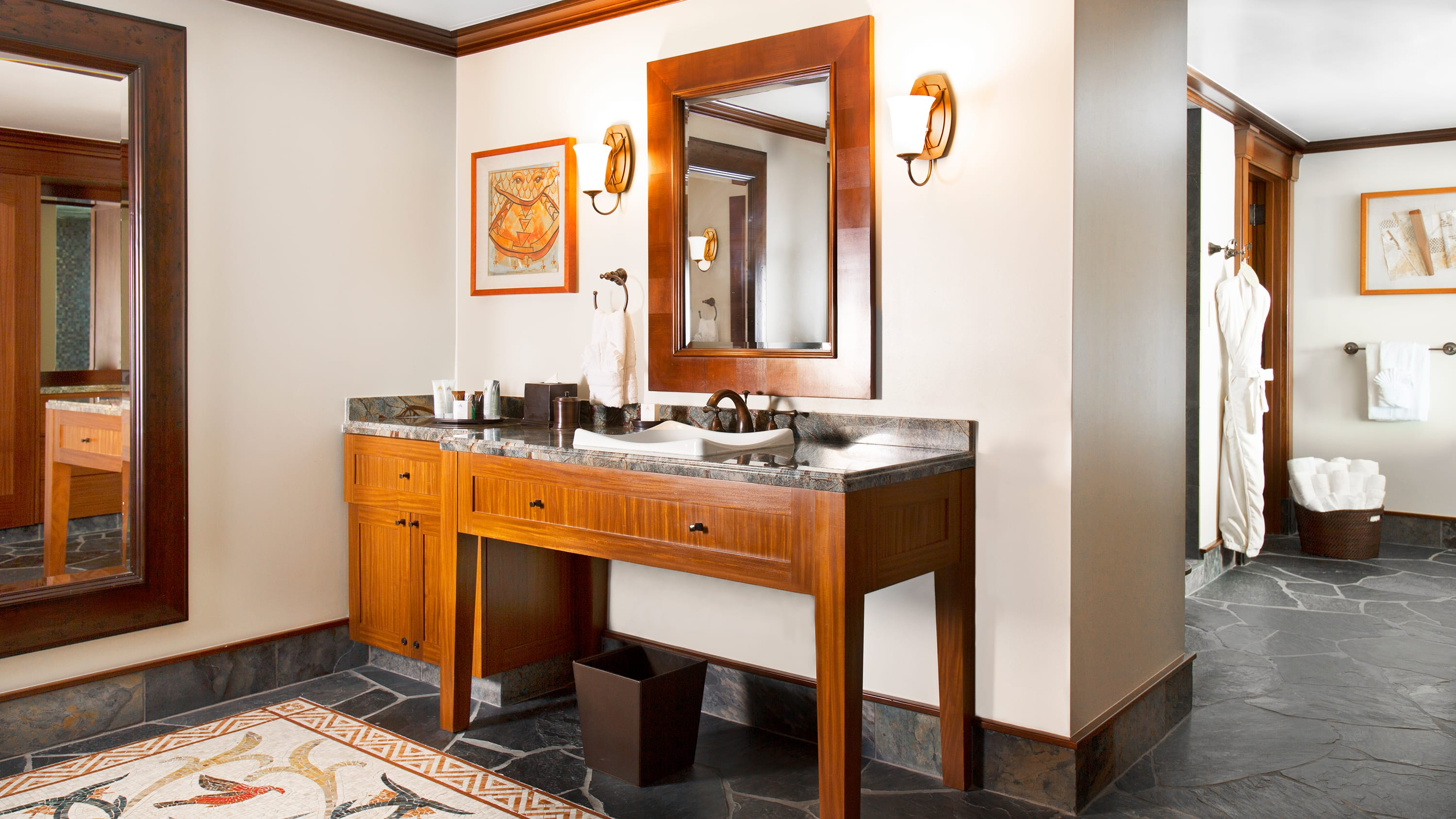 A bathroom area with a sink, towels, a mirror and toiletries near a robe