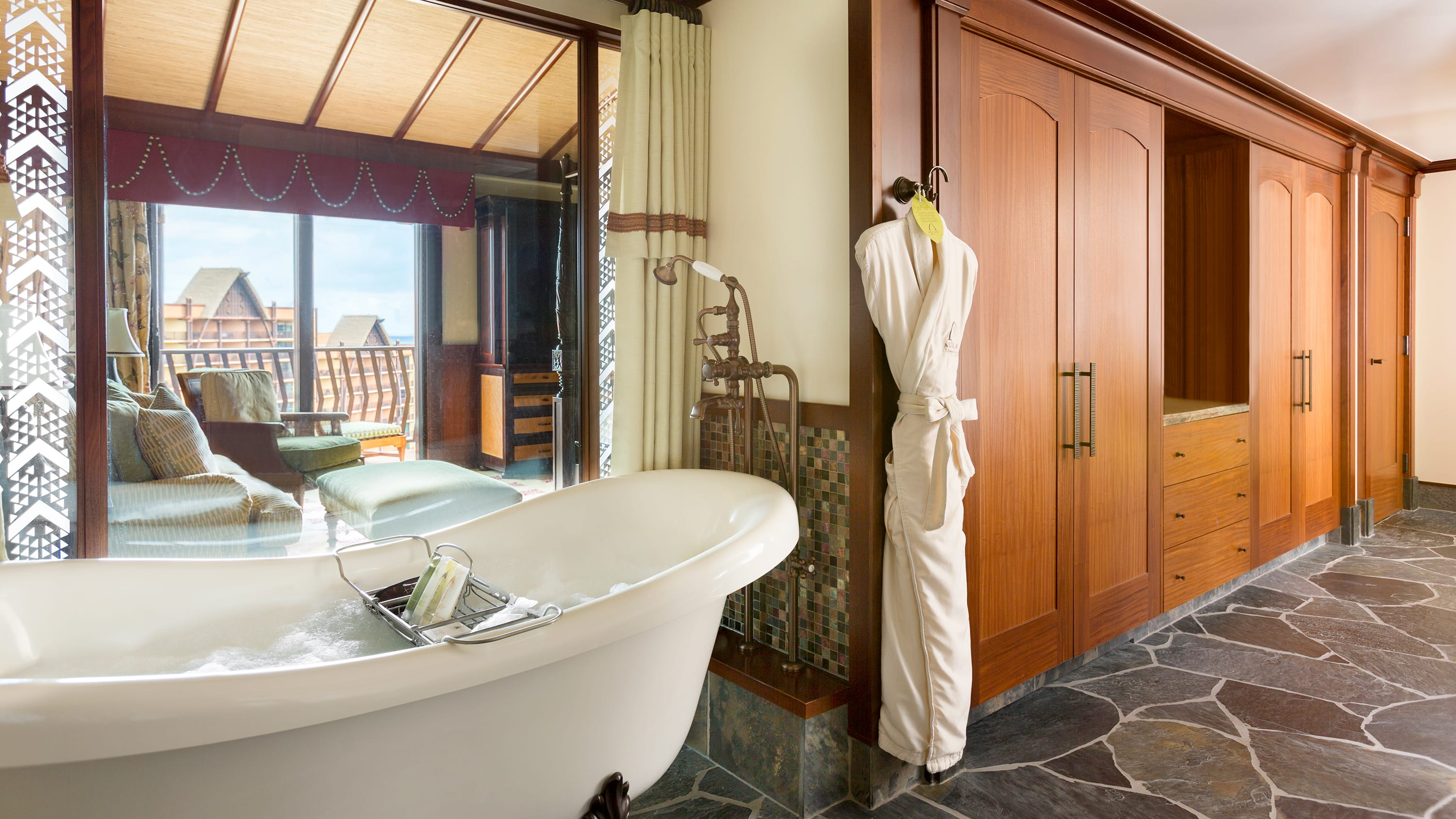 A robe, a bathtub and ashower near a window that looks into a room with a couch, a chair and balcony access