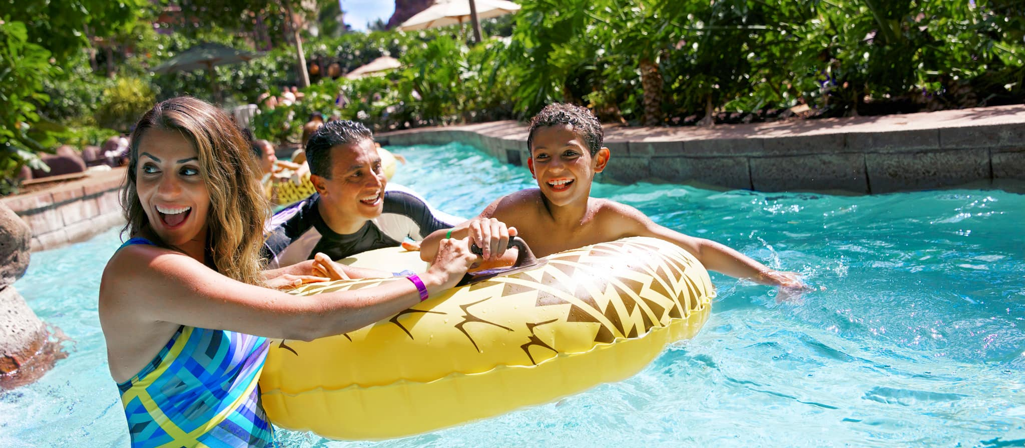 A smiling couple wades beside their daughter who rides an inflatable tube in Waikolohe Stream