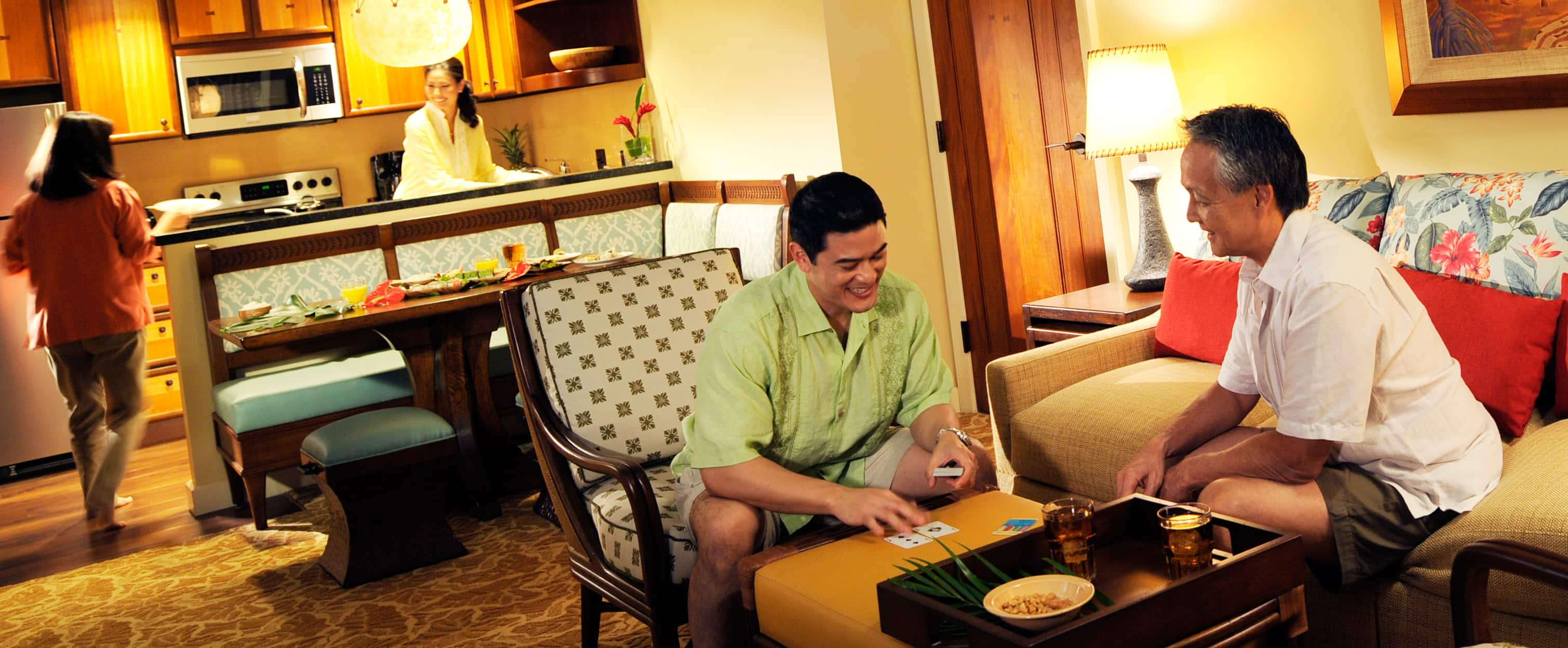 A family in the living area and kitchen of a 2-bedroom villa at Aulani Resort