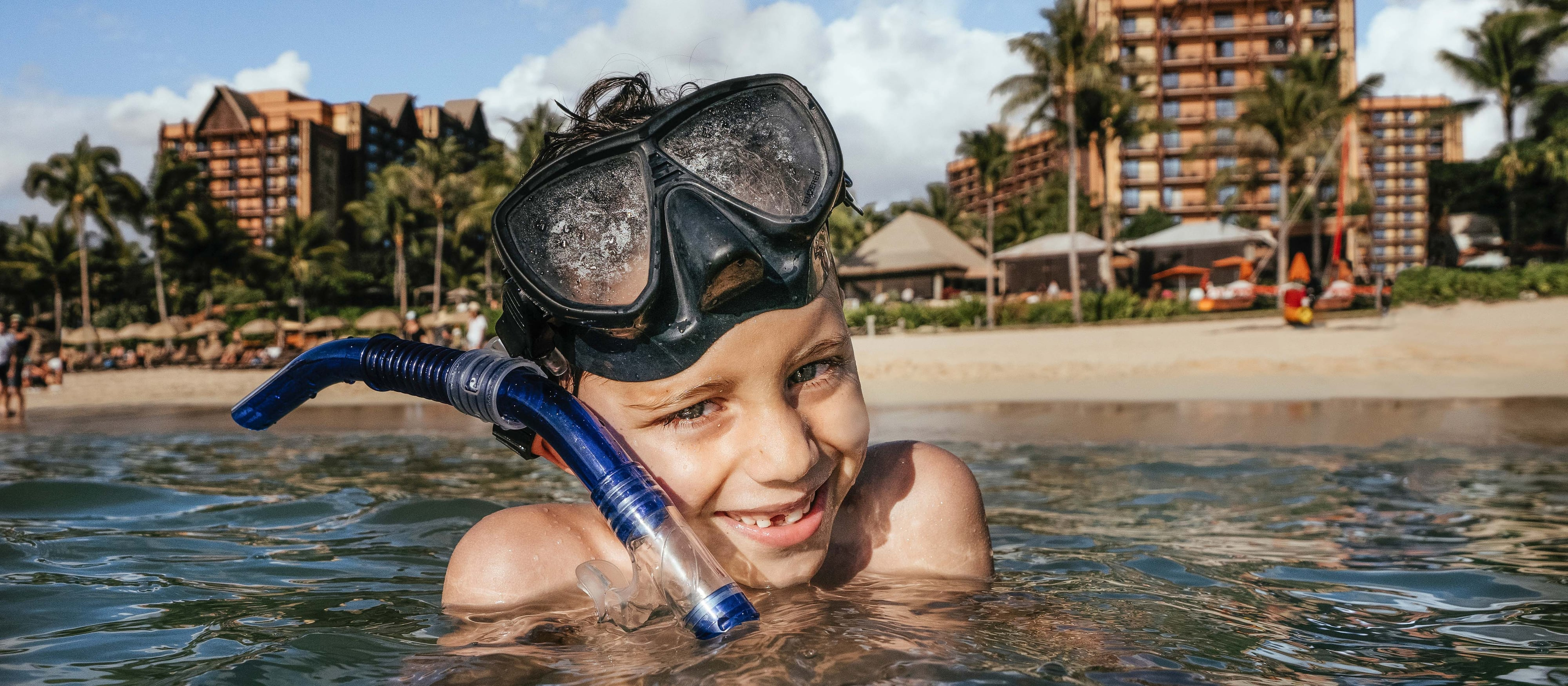 A boy wearing goggles and snorkeling equipment treads water in the ocean outside Aulani Resort