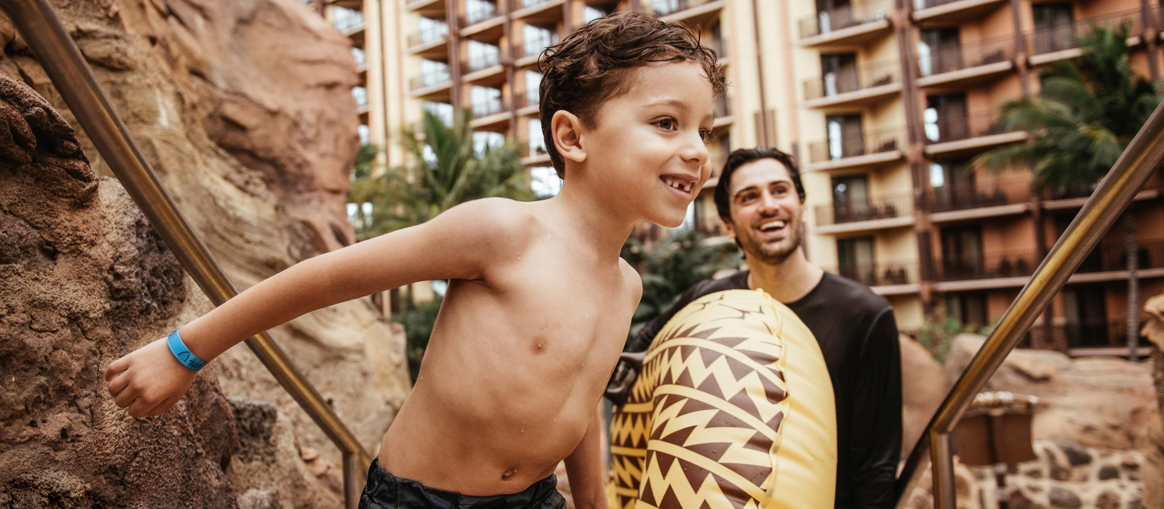 A father holding an inner tube and his son wearing swim trunks stand beside a rock at Aulani Resort