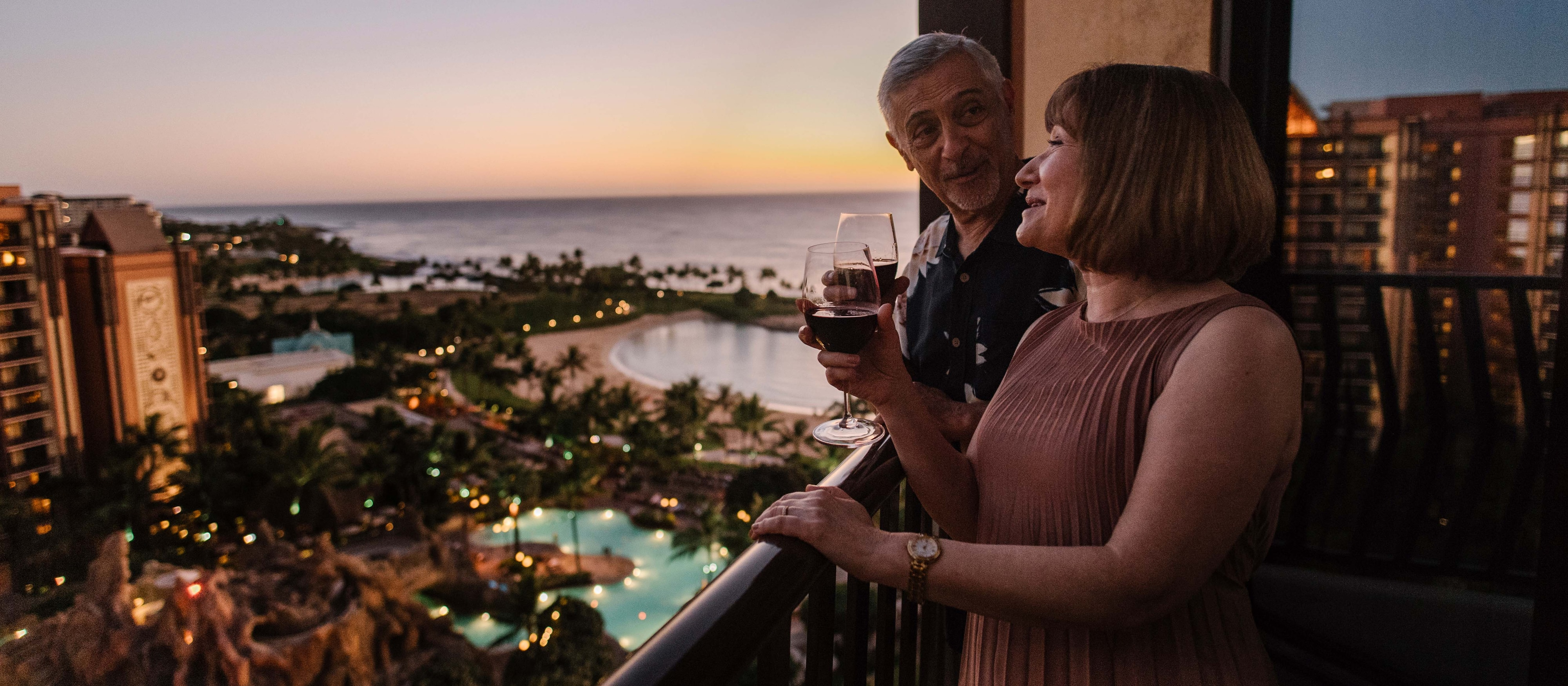 A mature couple drinks wine on a balcony overlooking pools and the ocean at Aulani Resort