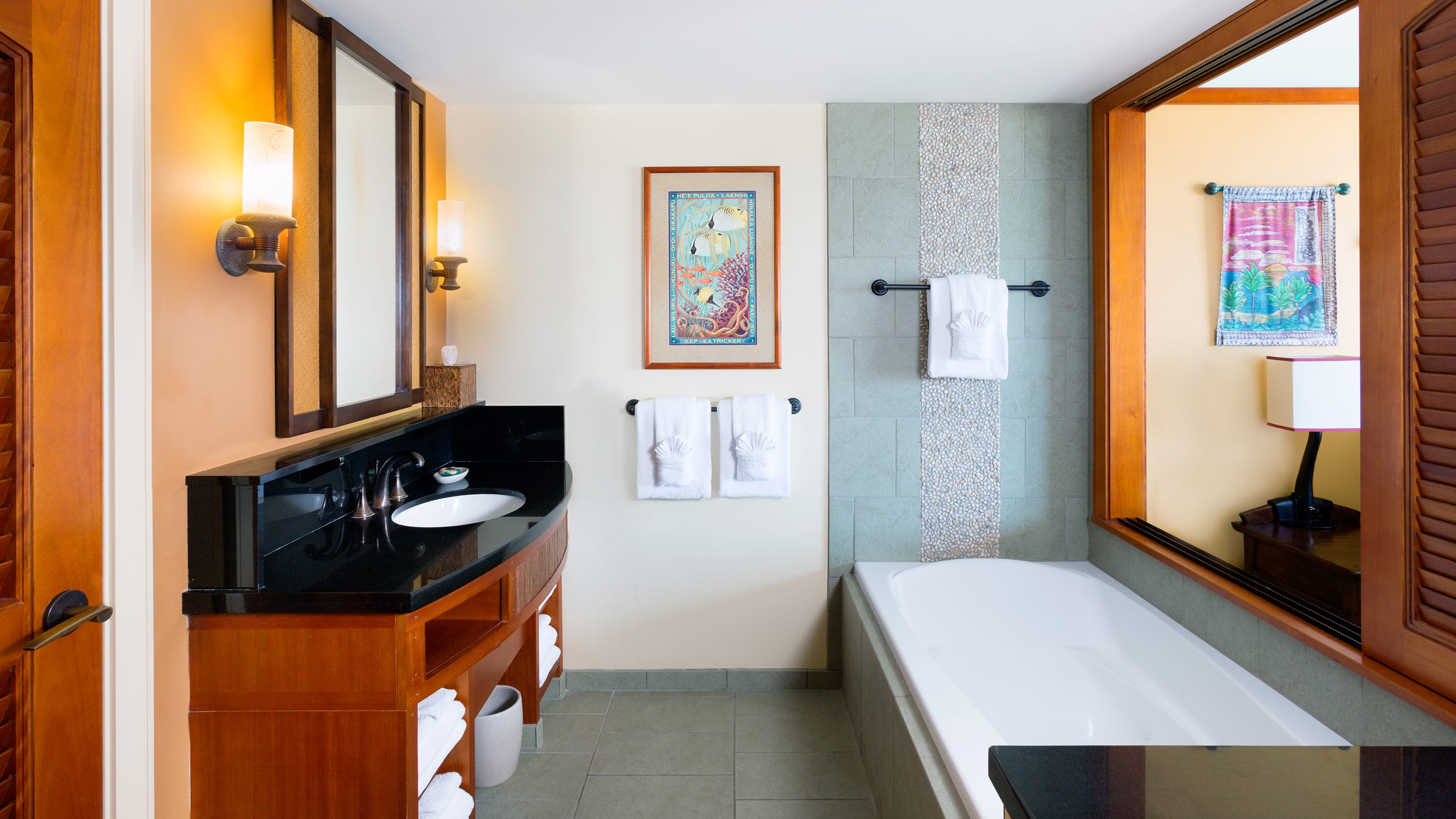 A bathroom with a sink, a mirror, towels, a painting and a bathtub near a room divider and a lamp